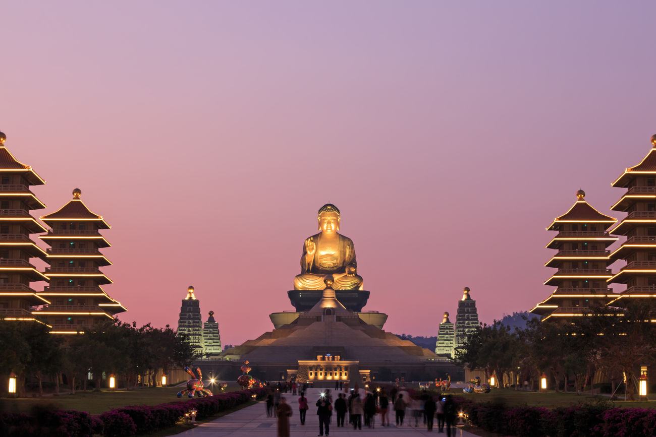 Kaohsiung, Taiwan - December 15, 2014: Sunset at Fo Guang Shan buddist temple of Kaohsiung, Taiwan with many tourists walking by. Architecture ASIA Asian  Asian Culture Buddha Buddha Statue Building Exterior Built Structure City City Life Clear Sky Crowd Fo Guang Shan Illuminated Kaohsiung Large Group Of People Leisure Activity Lifestyles Religion Summer Taiwan Tourism Tourist Tradition Travel Destinations