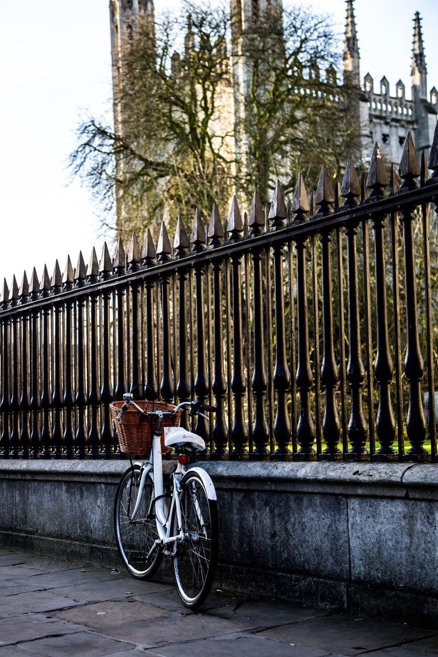 bicycle, railing, transportation, outdoors, tree, mode of transport, bridge - man made structure, day, architecture, city, land vehicle, built structure, building exterior, no people, stationary, sky