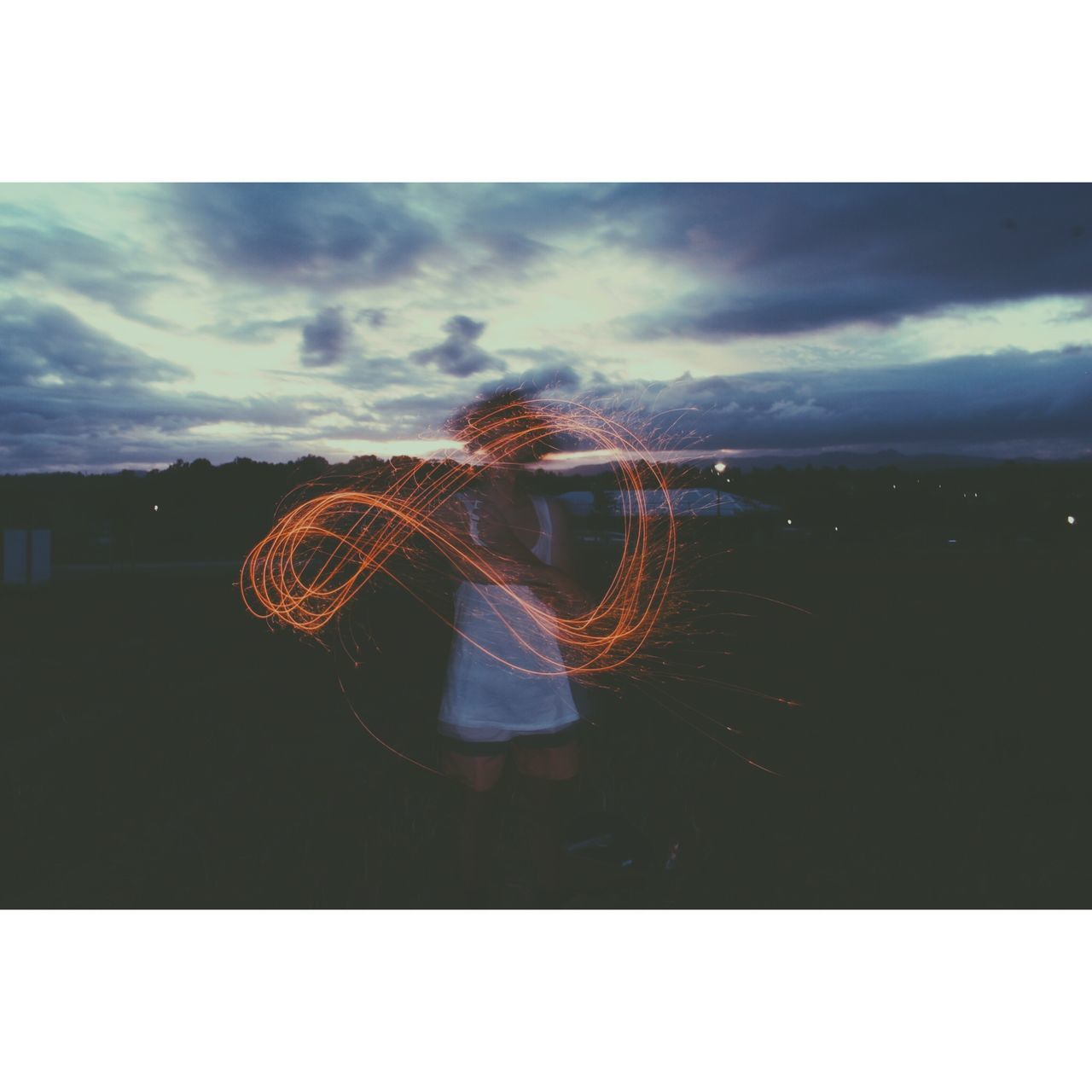 Woman Standing With Orange Light Painting Against Cloudy Sky