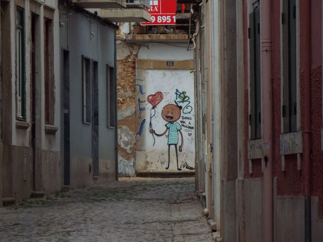 street art captured down a cobbled street in Faro, Portugal. Architecture Balloon Building Cobbled Street Faro Grafitti Grafitti Art. Grafitti Street Art Heart Love Heart Portugal Red Heart Stick Man Stickman Street Art Streetart