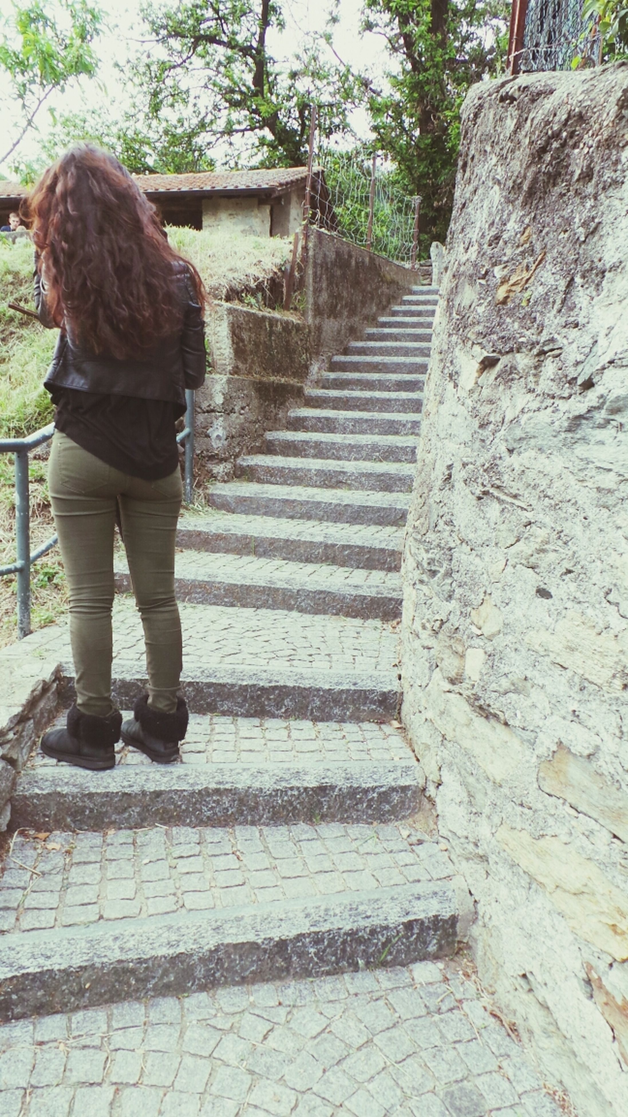 steps, lifestyles, leisure activity, full length, steps and staircases, casual clothing, rear view, built structure, standing, staircase, walking, architecture, person, the way forward, day, tree, railing, outdoors