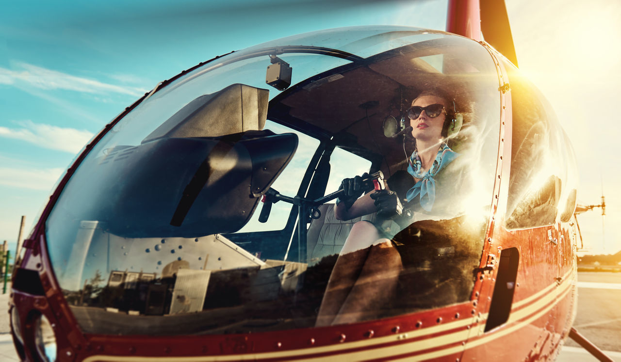 Attractive woman pilot sitting in the helicopter 30s Air Vehicle Aircraft Aircrew Airplane Aviator Business Woman Cabin Crew Caucasian Female Flight Headphones Helicopter Inside Landing Field Mode Of Transport One Person Outdoors People Pilot Sunglasses Sunlight Sunny Day Transportation Young Women