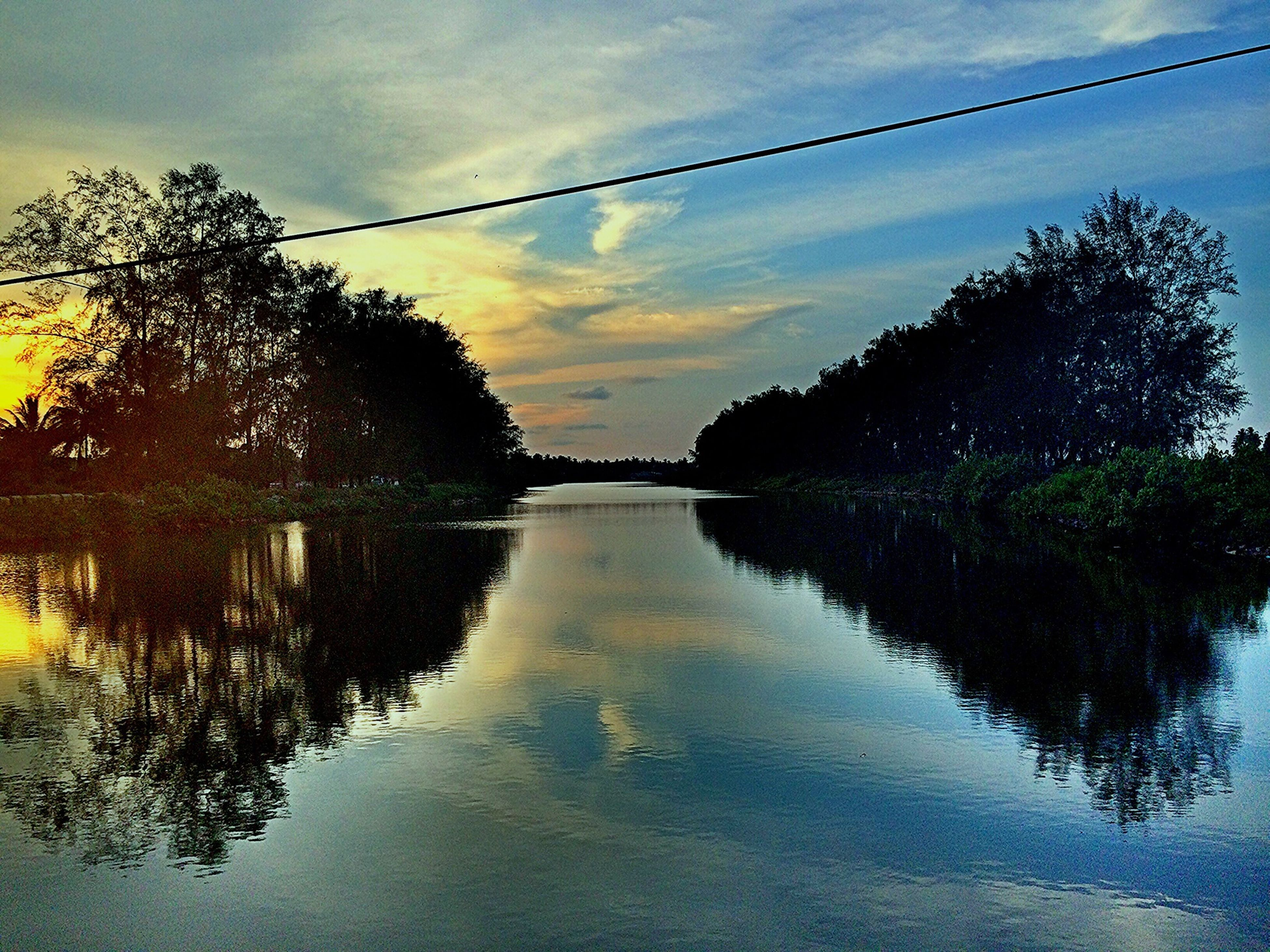 water, reflection, sky, tree, sunset, waterfront, tranquility, tranquil scene, cloud - sky, lake, river, scenics, beauty in nature, power line, nature, cloud, electricity pylon, rippled, outdoors, no people