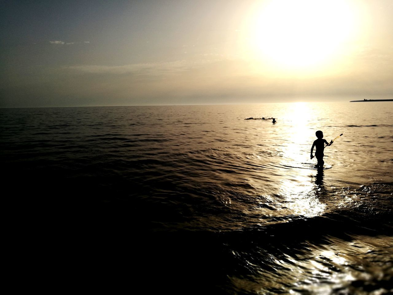sea, water, silhouette, horizon over water, sunset, scenics, nature, beauty in nature, tranquil scene, tranquility, waterfront, one person, sky, full length, rippled, beach, outdoors, standing, sunlight, real people, vacations, paddleboarding, day, people