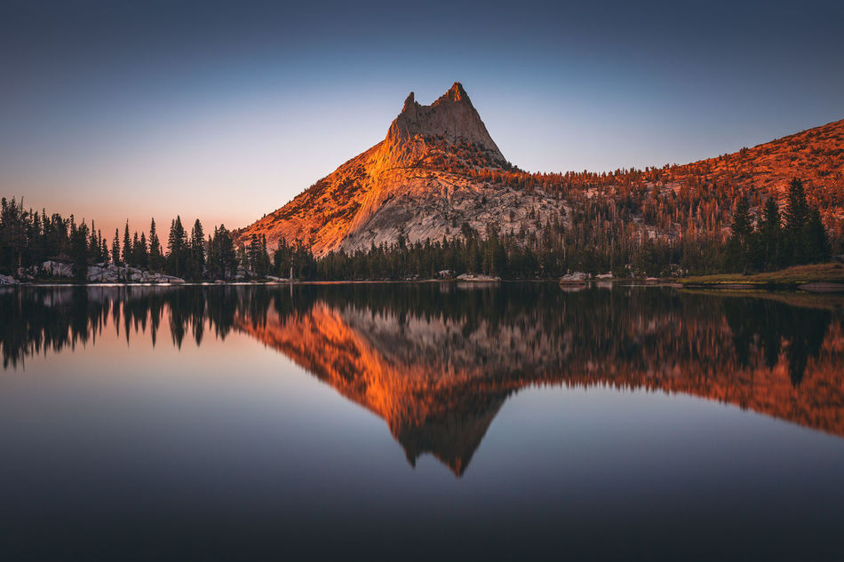 Reflection of gorgeous granite in water was dreamy | As the sun was sinking, a hint of warm, orange glow started infusing the blue sky. Cathedral Peak along with Eichorn Pinnacle lit up in orange. It was so bright and vivid that it felt like almost unreal. The reflection of the gorgeous granite in the water was dreamy. The lake was slowly fading into dim shade, and it was taking the forest with it. A moment that would evanesce in time. Like anything in life. A beautiful moment. And yet nothing stays beautiful forever. Yosemite National Park, CA Adventure Beauty In Nature Cathedral Peak Forest Granite John Muir Trail Lake Landscape Landscape Photography Mountain Mountain Peak Nature No People Orange Hue Outdoors Reflection Sierra Nevada Sky Sunset Sunset Glow Tranquility Upper Cathedral Lake Water Wilderness Yosemite National Park