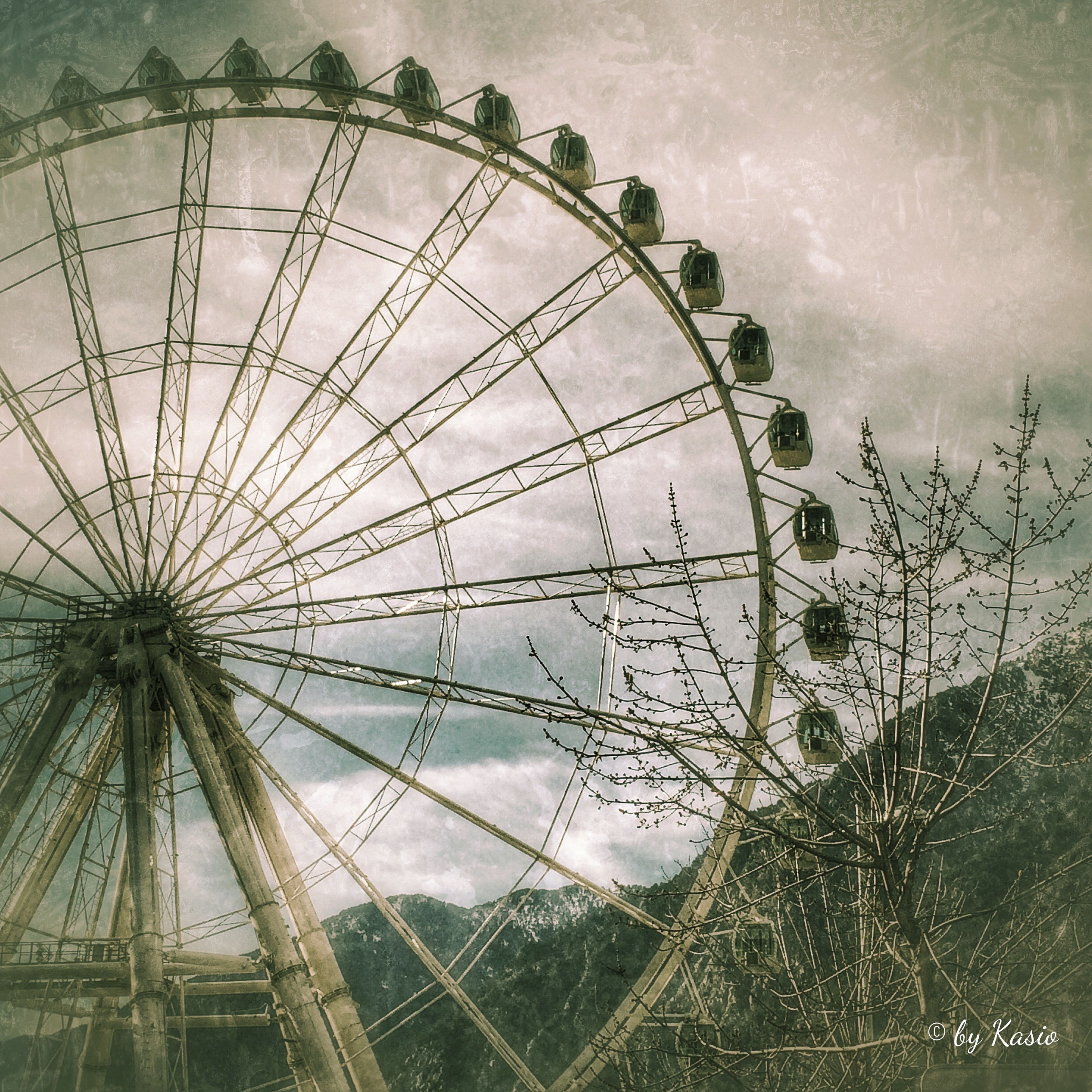 ferris wheel, amusement park, amusement park ride, low angle view, sky, arts culture and entertainment, cloud - sky, built structure, day, outdoors, circle, cloudy, cloud, architecture, no people, nature, multi colored, metal, pattern, fun