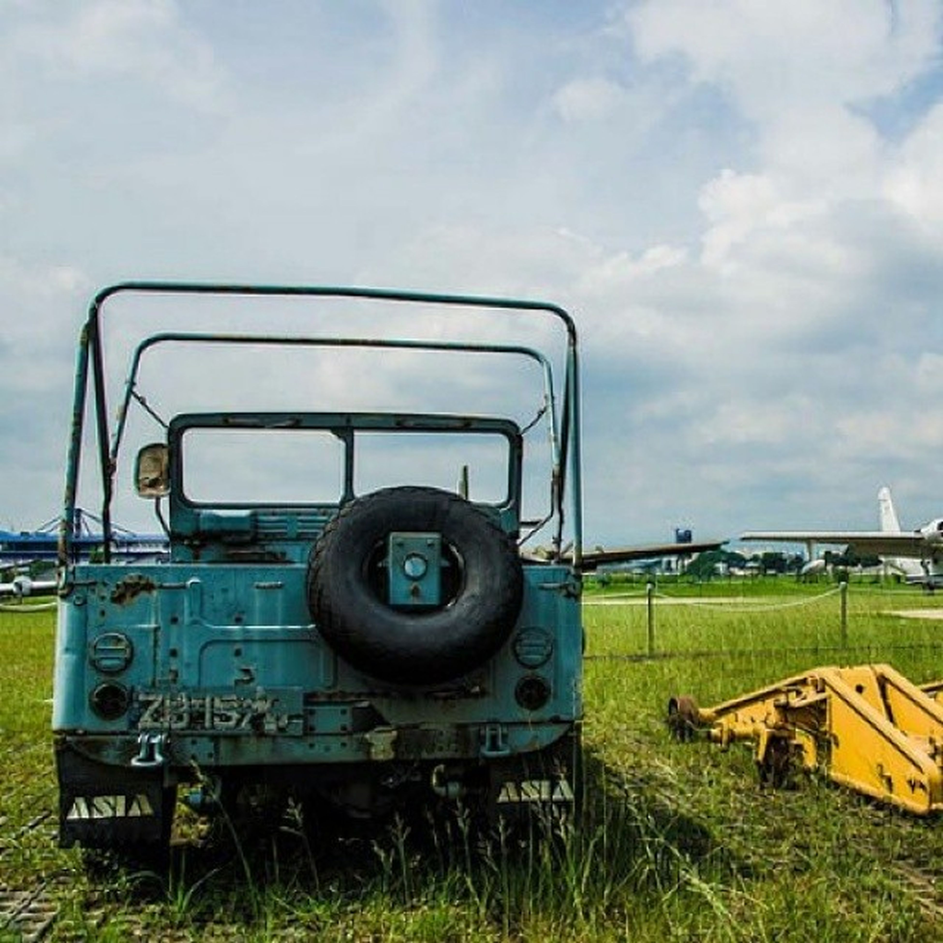 grass, field, sky, transportation, mode of transport, cloud - sky, land vehicle, green color, grassy, landscape, day, abandoned, metal, tractor, no people, outdoors, agriculture, cloud, rural scene, nature