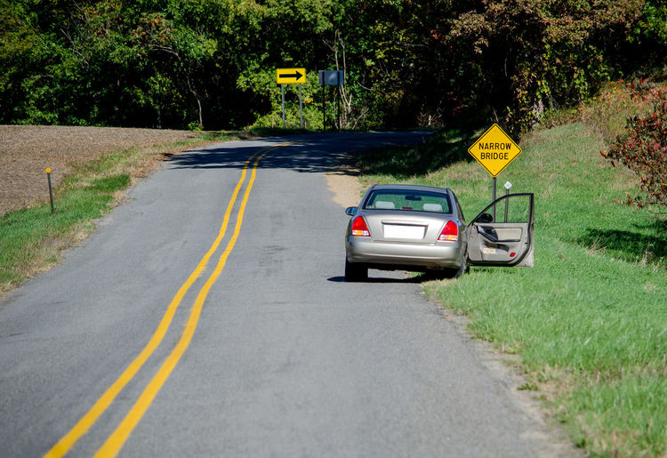 an abandoned car sits discarded along a rural road with a door open and people missing. something looks suspicious! Foul Play Rural USA Abandoned Car Car Danger Day Deserted Driving Journey Nature No People No People, Opened Car Door Outdoors Road Suspicious Activity The Way Forward Transportation Travel