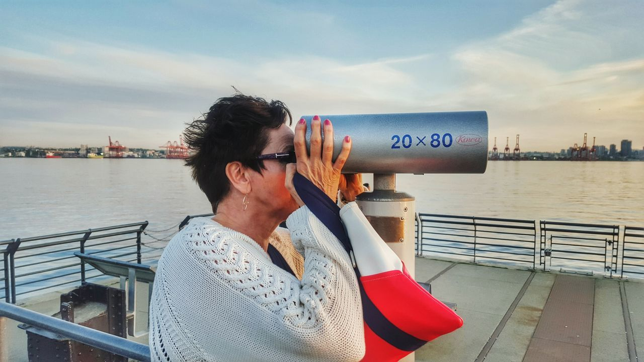 EyeEm Selects One Woman Only Adult Water Looking Looking Through Looking Out Travel Destination Outdoors Sky British Columbia, Canada Telescope Telescope Photo Telescope Viewer One Person Communication Cloud - Sky People Pier Dock Industry Shipyards The Week On EyeEm