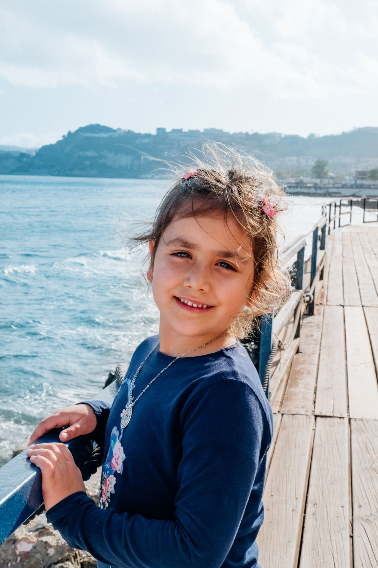 little girl candid image of happyness to be at sea Beauty In Nature Candid Portraits Child Childhood Day Elementary Age Girl Happiness Leisure Activity Lifestyles Looking At Camera Naples, Italy One Person Outdoors Portrait Promenade Real People Sea Sky Smiling Standing