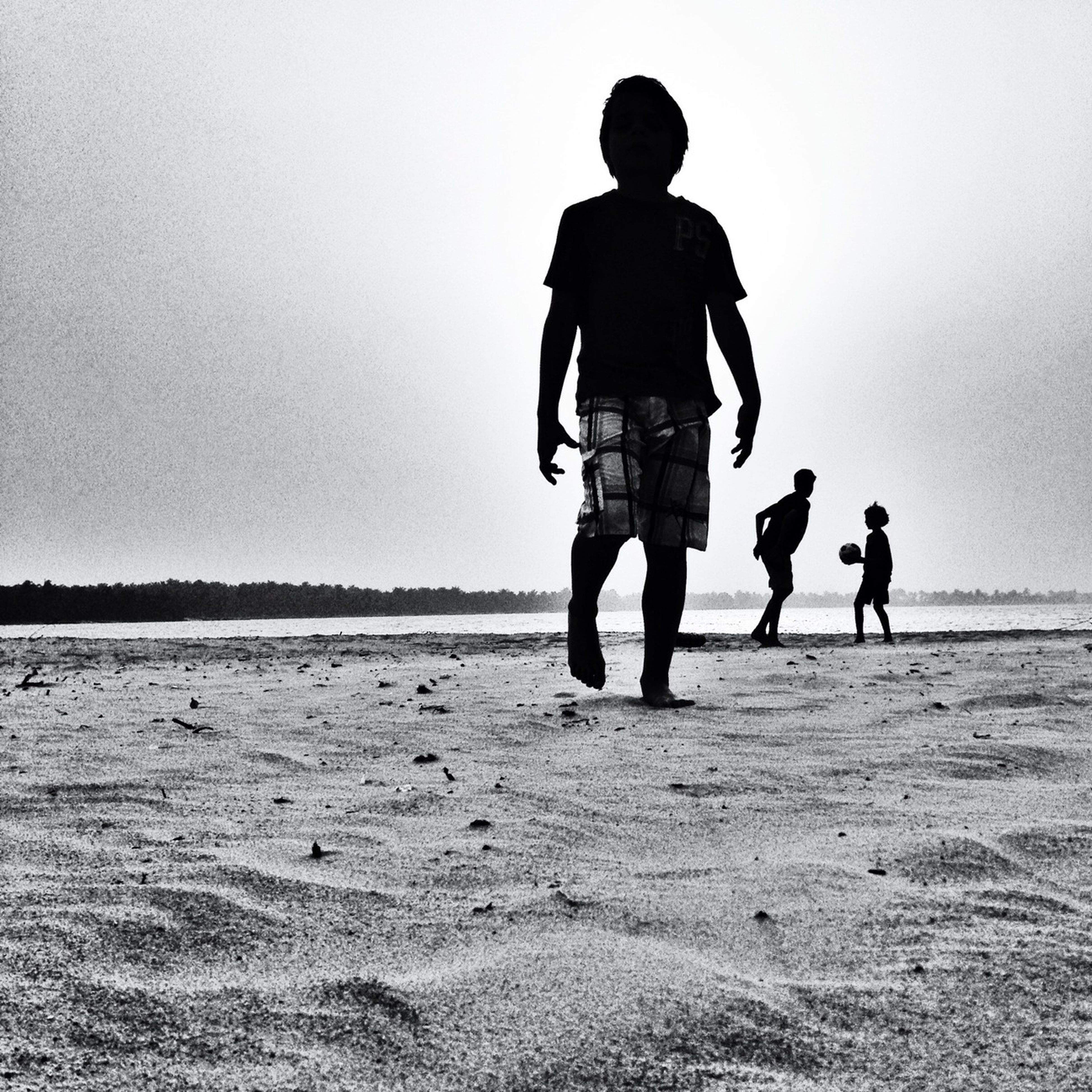 full length, beach, lifestyles, leisure activity, rear view, clear sky, childhood, sand, men, togetherness, walking, boys, copy space, standing, sea, casual clothing, shore, bonding