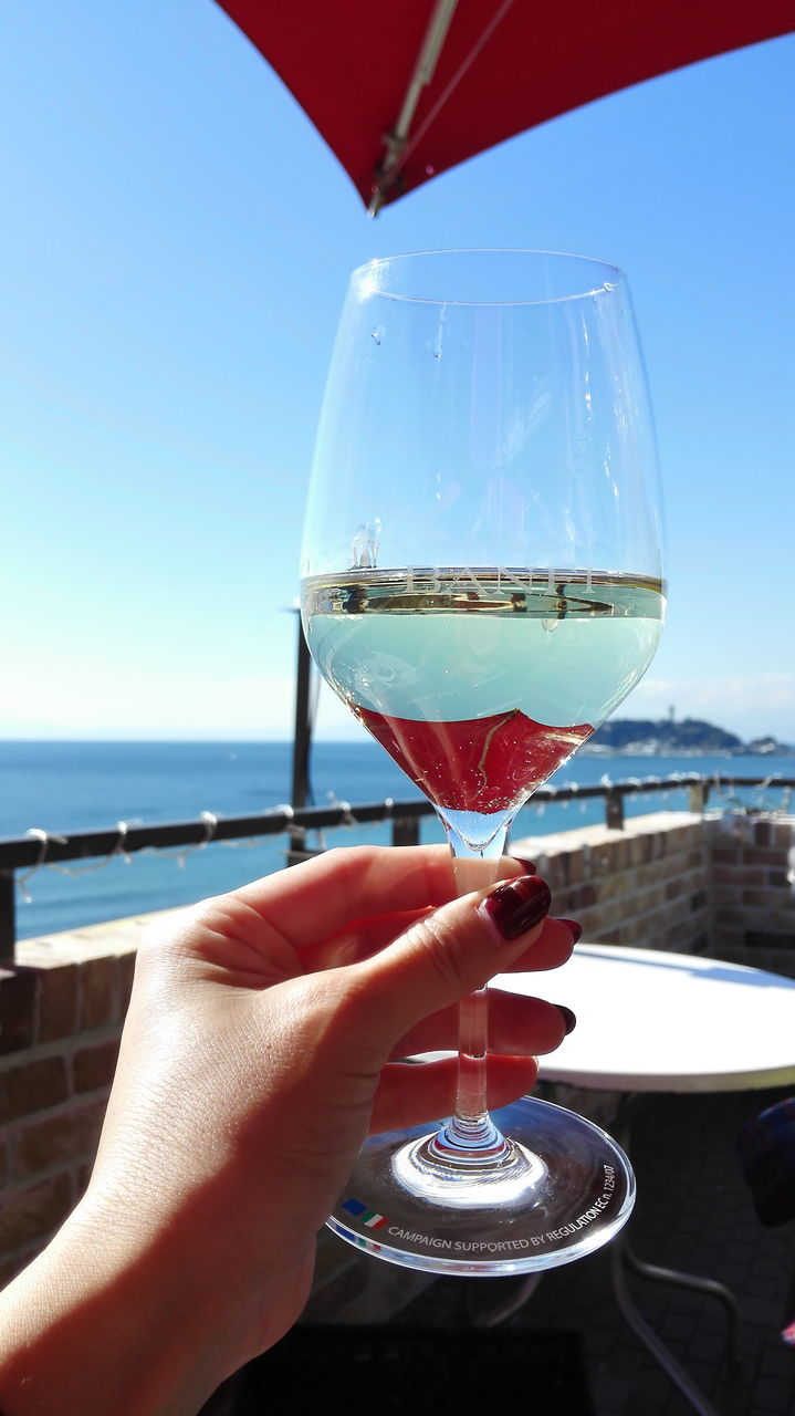 Hand Holding Wine Glass Against Blue Sky
