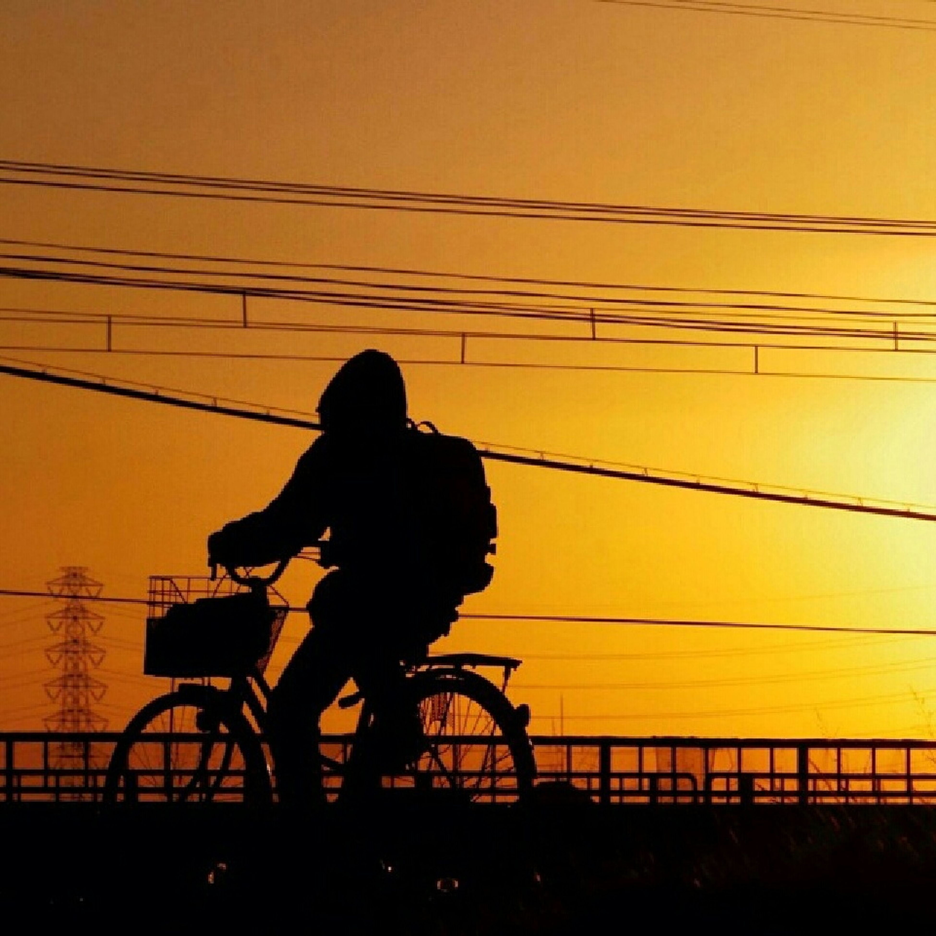 silhouette, sunset, lifestyles, orange color, leisure activity, men, standing, railing, connection, full length, sky, power line, rear view, cable, side view, person, electricity pylon, built structure