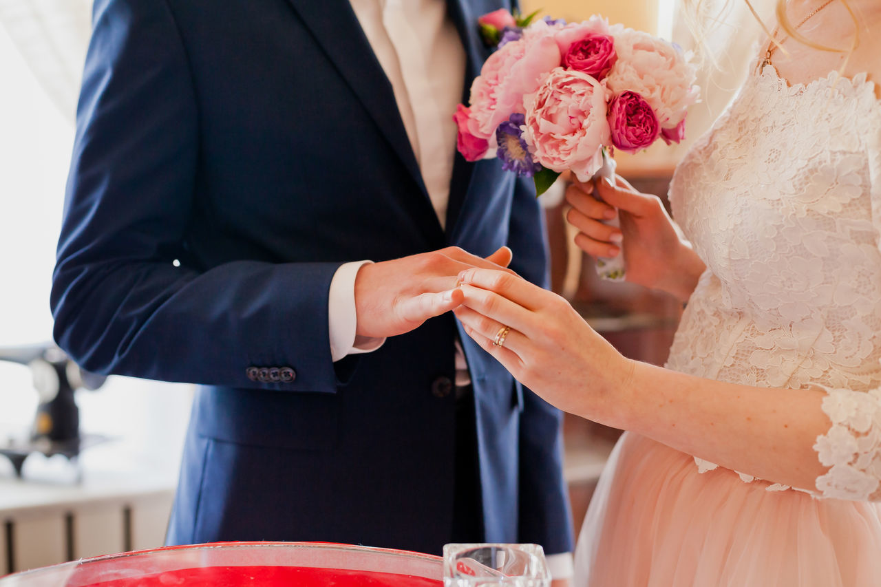 Bouquet Bride Bridegroom Celebration Celebration Event Ceremony Close-up Day Flower Groom Holding Human Hand Indoors  Life Events Men Midsection Real People Standing Togetherness Two People Wedding Wedding Ceremony Wedding Dress Well-dressed Women