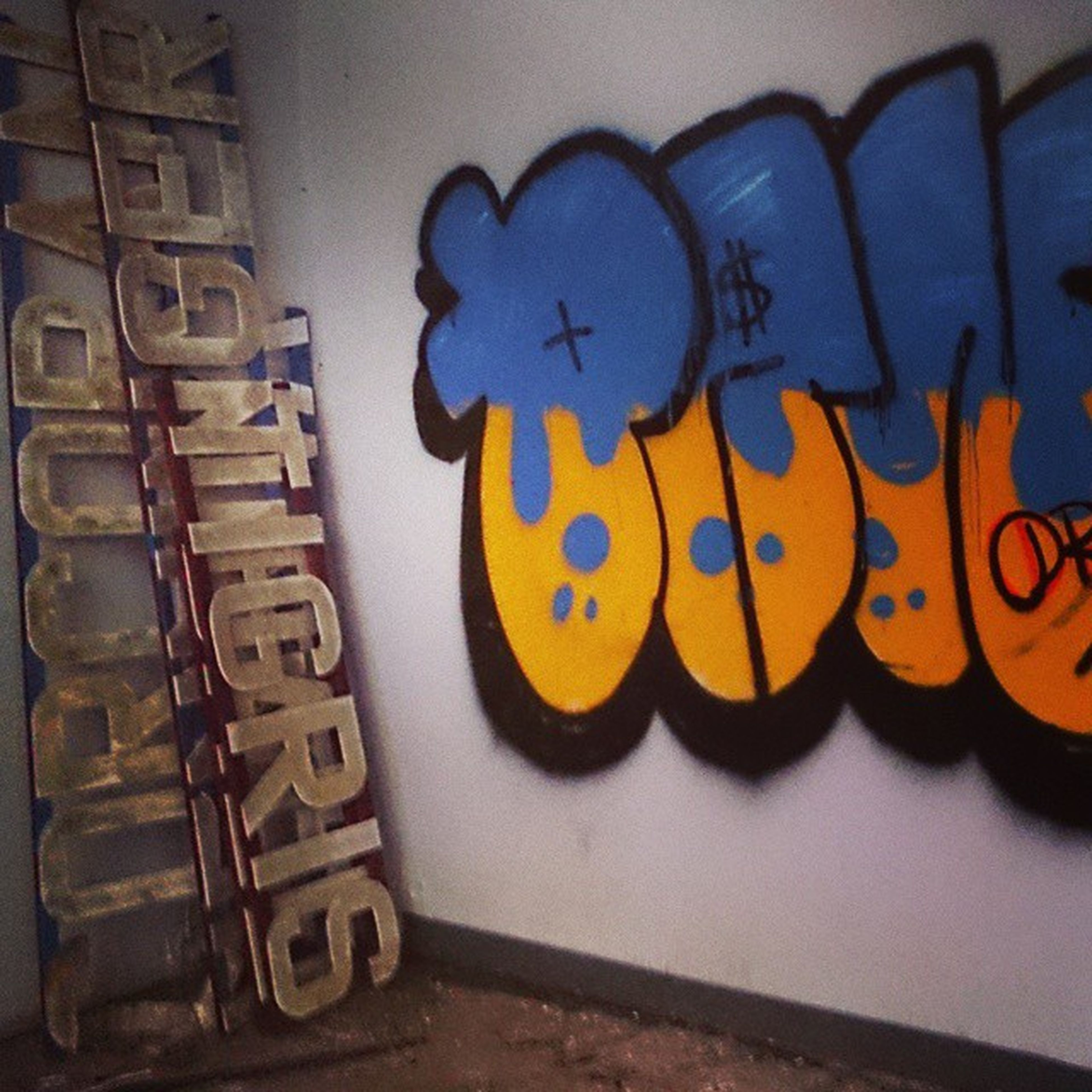 indoors, art and craft, creativity, art, multi colored, close-up, wall - building feature, yellow, still life, no people, text, animal representation, communication, variation, human representation, table, graffiti, high angle view, western script, craft