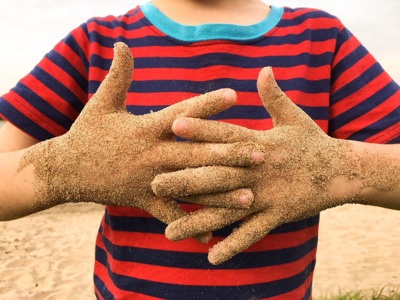 Midsection Of Boy With Dirty Hands Clasped At Sandy Beach