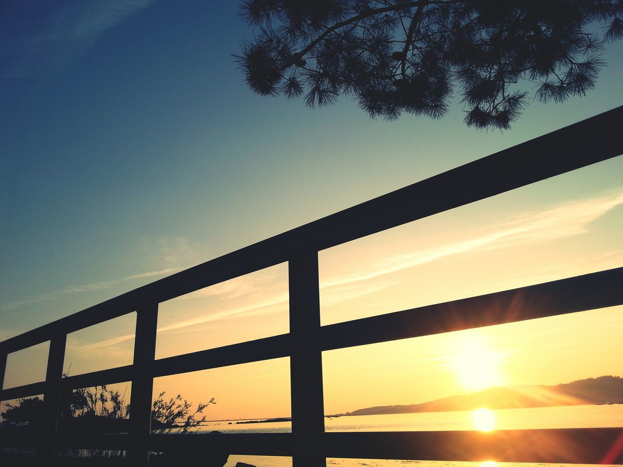 Low Angle View Of Railing By Sea At Sunset