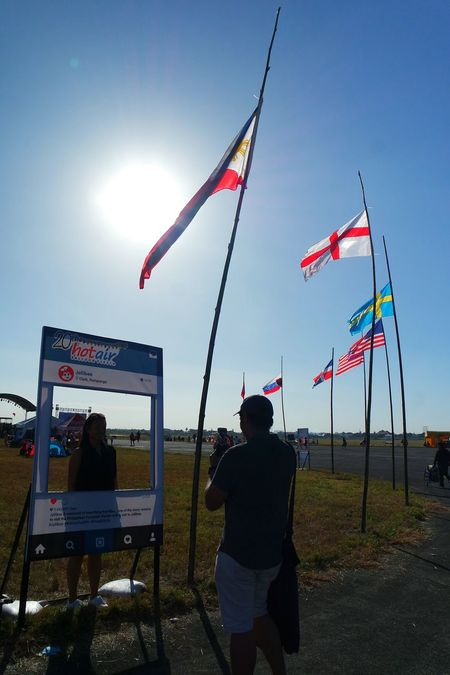 Couple taking a picture at the photo booth PIHABF2016 Philippineinternationalhotairballoonfestival Balloonfestph Under The Sun Photobooth Couple Couples Shoot Flags In The Wind  Pampanga Eyeem Philippines Taking Photos Photoshooting Someoneelse Taking Photos Of People Taking Photos
