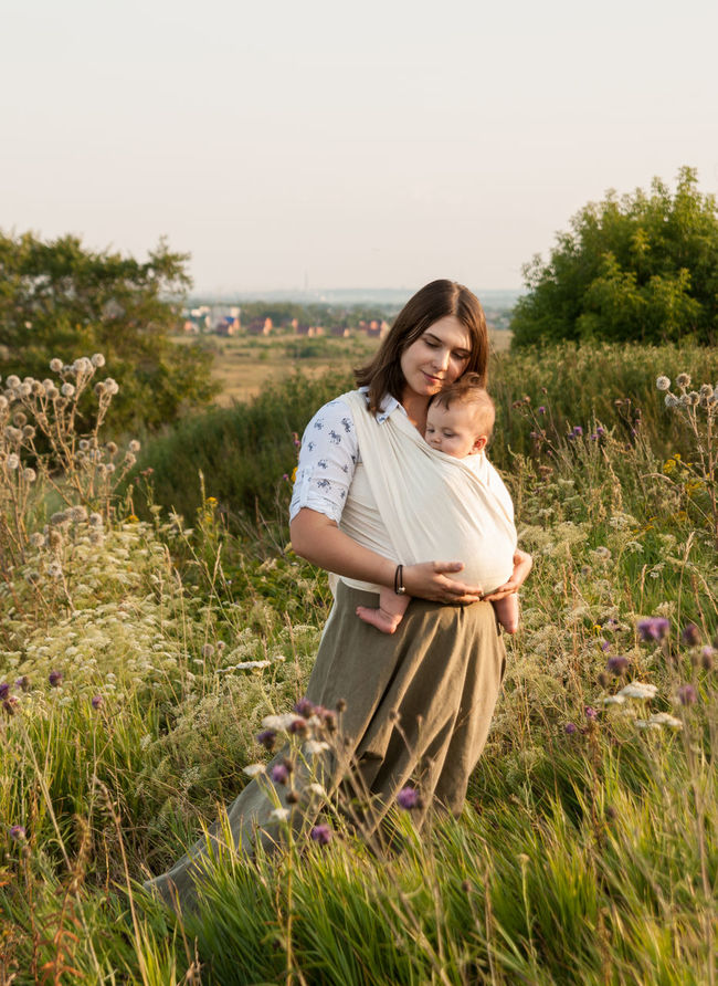Natural parenting and never-ending love Baby Baby Sling Baby Wrap Babywearing Bonding Carefree Childhood Children Family Field Golden Hour Grass Happiness Lifestyle Love Maternity Mom Mother And Son Motherhood Outdoors Parenting Sling Smiling Summer Woman