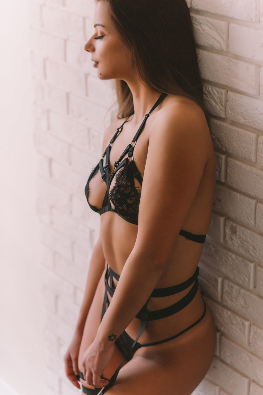 one person, wall - building feature, brick wall, young adult, young women, real people, beautiful woman, standing, leisure activity, lifestyles, lingerie, side view, beauty, indoors, day