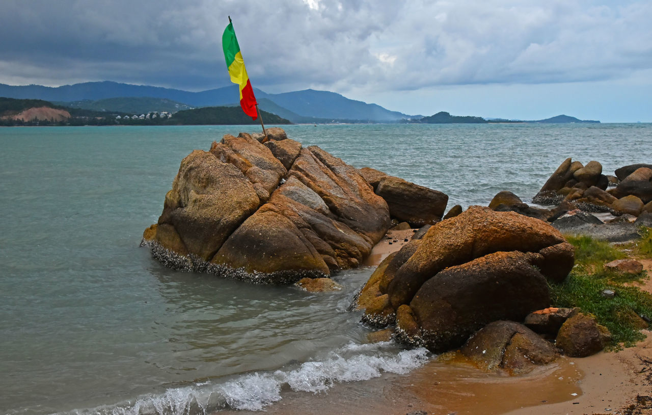 Rastafari Pan-African flag in coastline stone at fisherman's village at Koh Samui, Thailand African Cloudy Skies EyeEm Thailand Fisherman Flag Freedom Koh Samui Landscape Landscape_Collection Landscape_photography Legalizeit RASTA Rastafari Sea Storm Thailand Thailand_allshots Travel Travel Photography Travelphotography Village Landscapes With WhiteWall Spotted In Thailand The KIOMI Collection