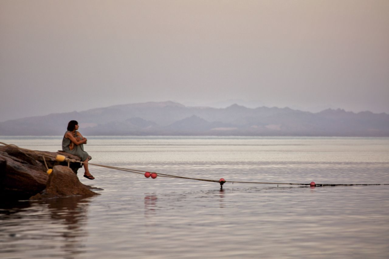 water, nature, real people, oar, sea, tranquility, leisure activity, scenics, beauty in nature, mountain, outdoors, day, tranquil scene, two people, sitting, sky, men, full length, nautical vessel, standing, wooden raft, rowing, clear sky, paddleboarding, people