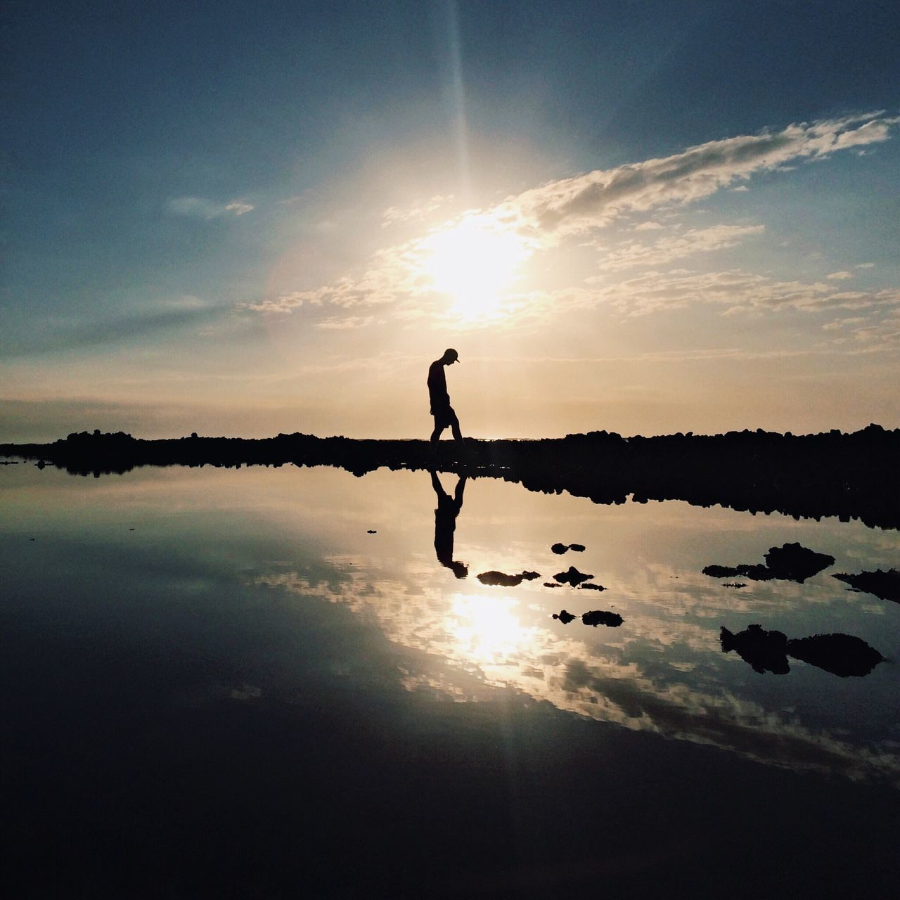 Silhouette Reflection Sunset Sun Water Sky Sunlight Lake Sunbeam Beauty In Nature Tranquil Scene Nature Tranquility Scenics Outdoors One Person Standing Balance Side View Cloud - Sky