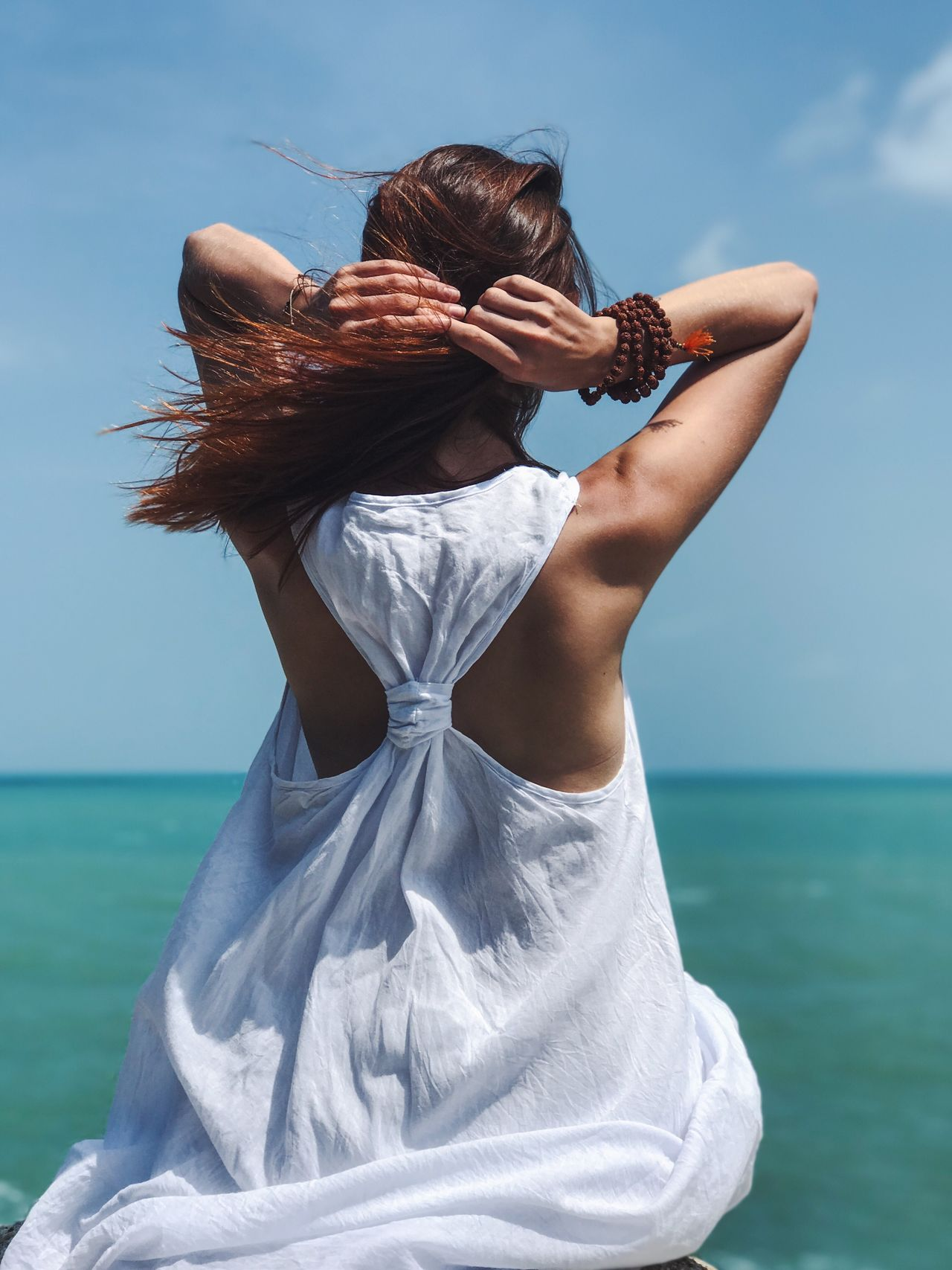 Sea Real People Horizon Over Water Water Rear View One Person Sky Leisure Activity Outdoors Lifestyles Beach Nature Day Women Long Hair Sitting Rock - Object Blue Beauty In Nature Scenics Young Women The Portraitist - 2017 EyeEm Awards White Dress Human Back Bracelet