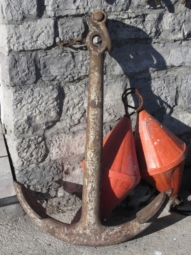 A rusty anchor and two orange conical buoys at the marina Aged Anchor Buoys Conical Corroded Danger Demarcation Dock Equipment Harbor Heavy Iron Lifesaver Marina Marine Maritime Nautical Navigation Object Orange Rusty Safety Sailor Security Warning