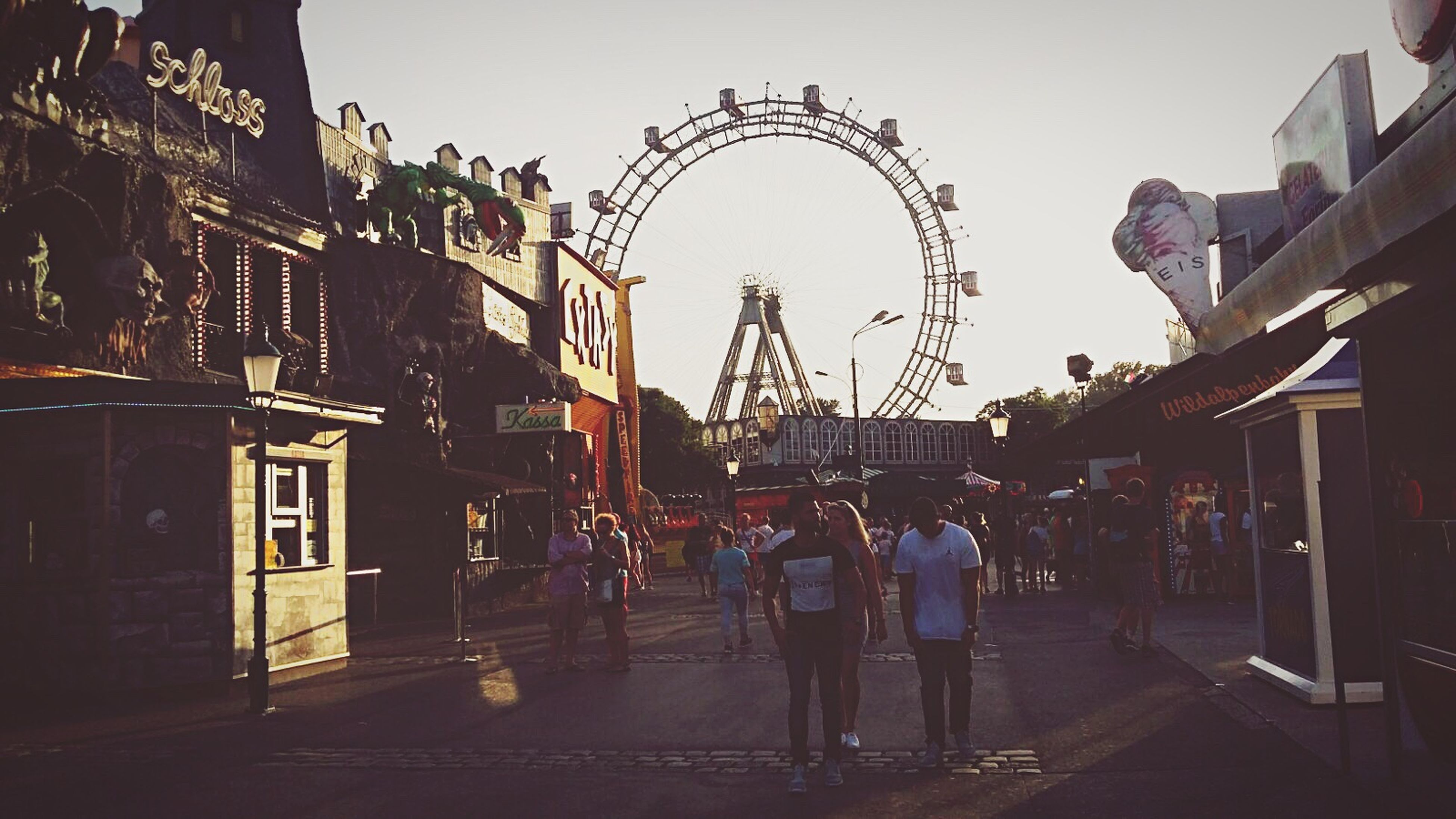 architecture, built structure, building exterior, ferris wheel, amusement park, city life, walking, clear sky, city, leisure activity, street, amusement park ride, person, group of people, city street, day, sky, outdoors, pedestrian, narrow