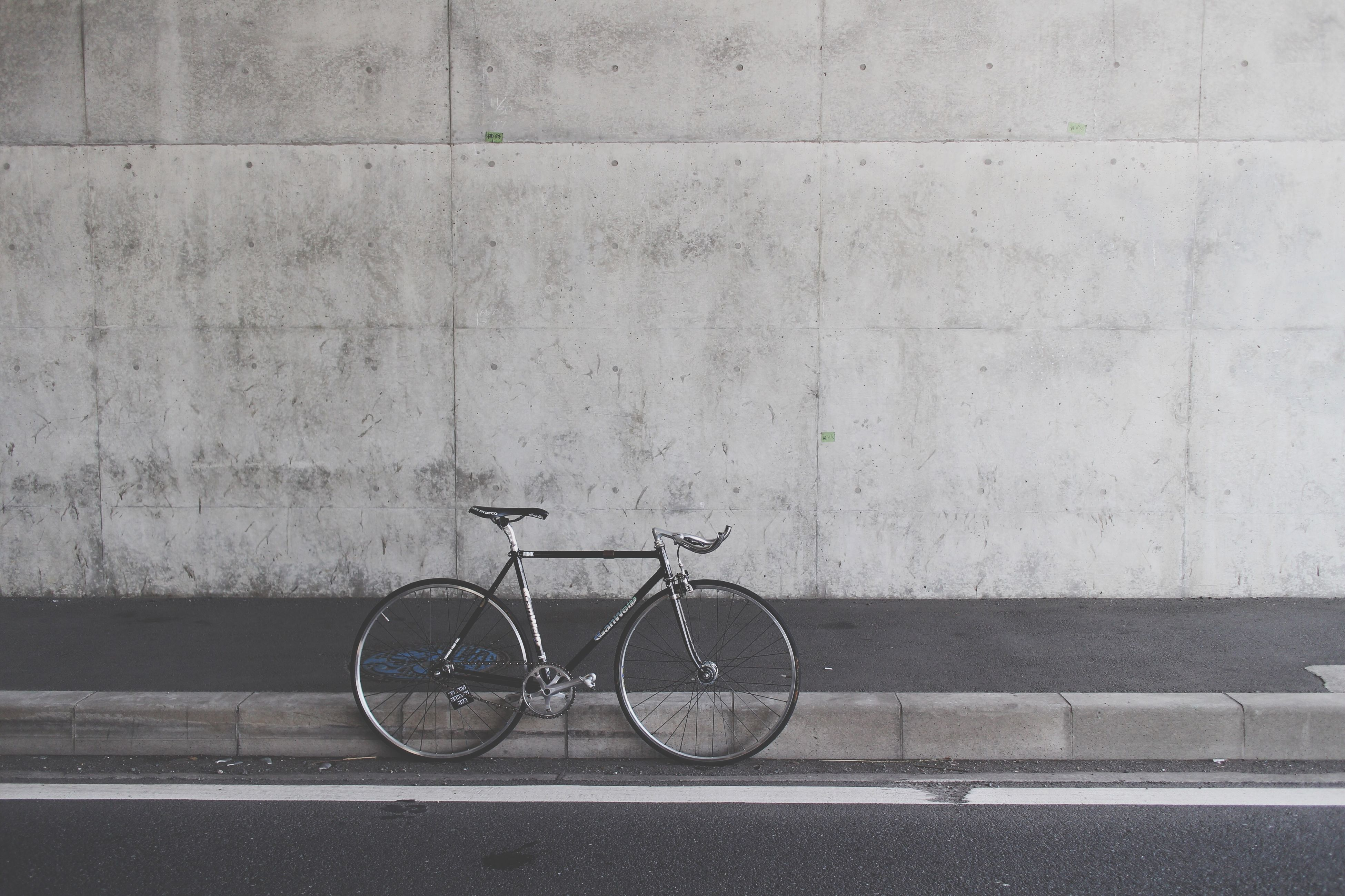 bicycle, transportation, land vehicle, mode of transport, stationary, parked, parking, street, built structure, wall - building feature, cycle, road, sidewalk, day, outdoors, architecture, building exterior, wheel, no people, side view