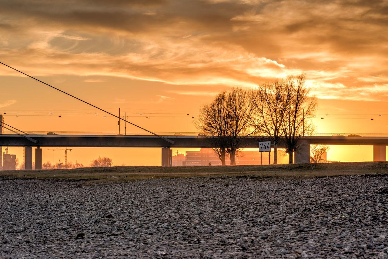 DUESSELDORF, GERMANY - JANUARY 20, 2017: Scenic sundset over a Rhine Bridge Agriculture Bridge Cloud - Sky Colorful Day Düsseldorf Nature No People Orange Orange Color Outdoors Scenics Shadow Sky Sunlight Sunset Tree Trees
