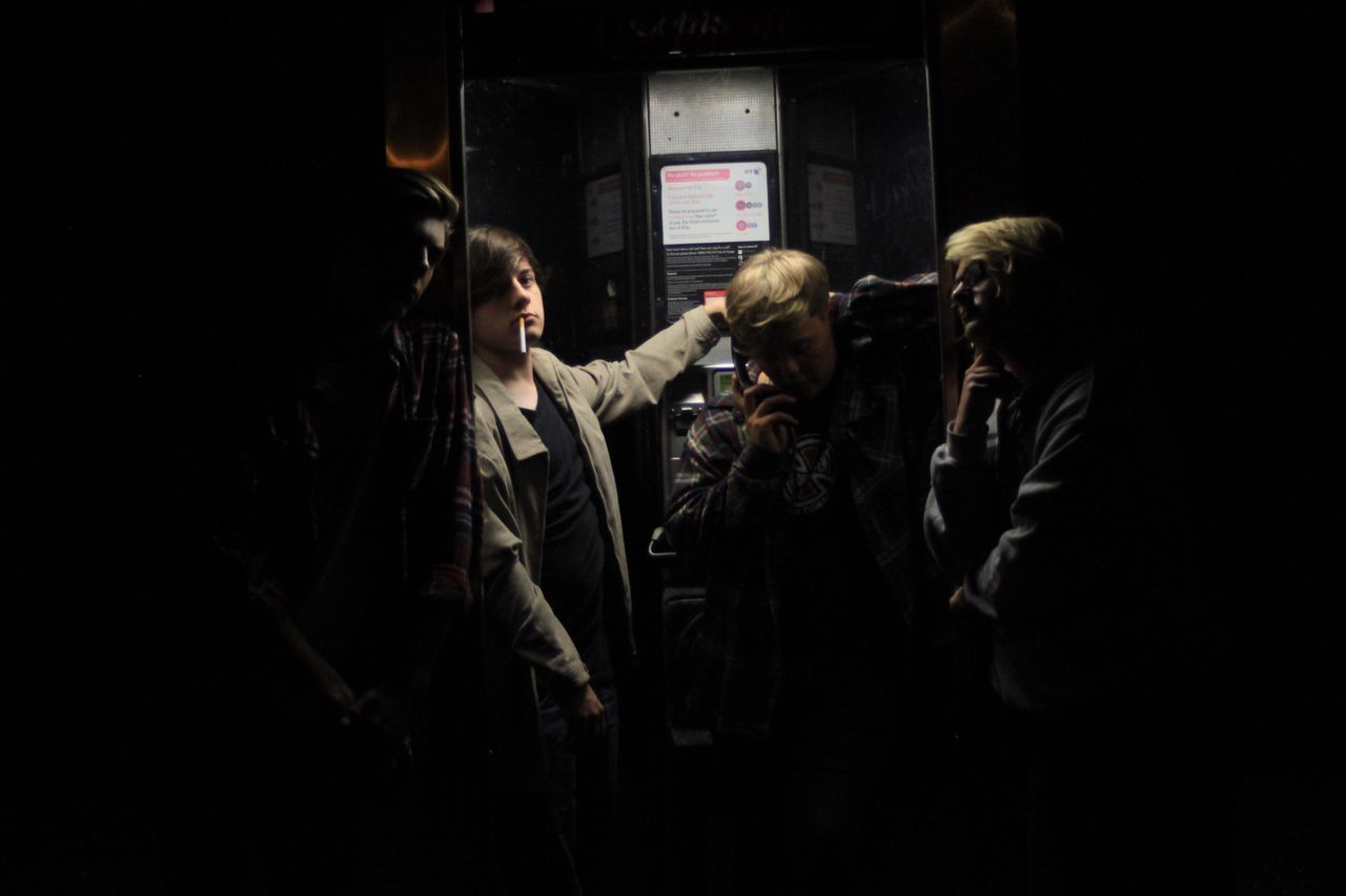 Dark Nightlife Phonebooth Night Young Adult Casual Clothing Black Background Friendship Group Group Shot Street Streetphotography Looking At Camera Cigarette  Low Light Dark Straight Angle Mood Lighting  Mood Light Composition Casual Fun Friends Drinking Smoking
