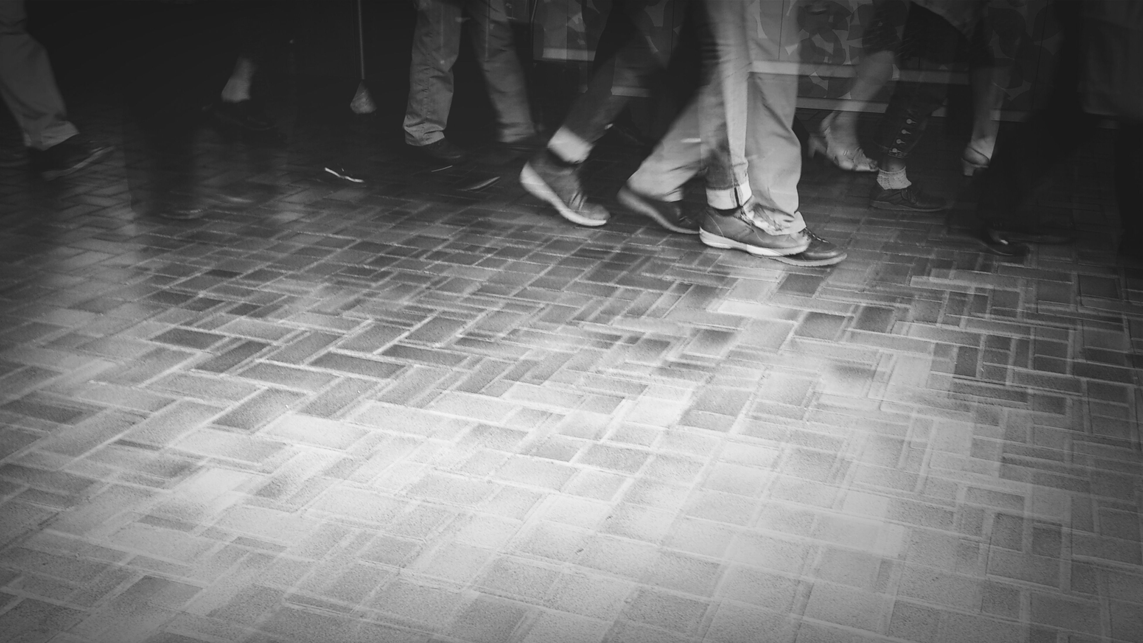 low section, person, indoors, lifestyles, men, tiled floor, flooring, standing, leisure activity, walking, human foot, high angle view, unrecognizable person, shoe, medium group of people