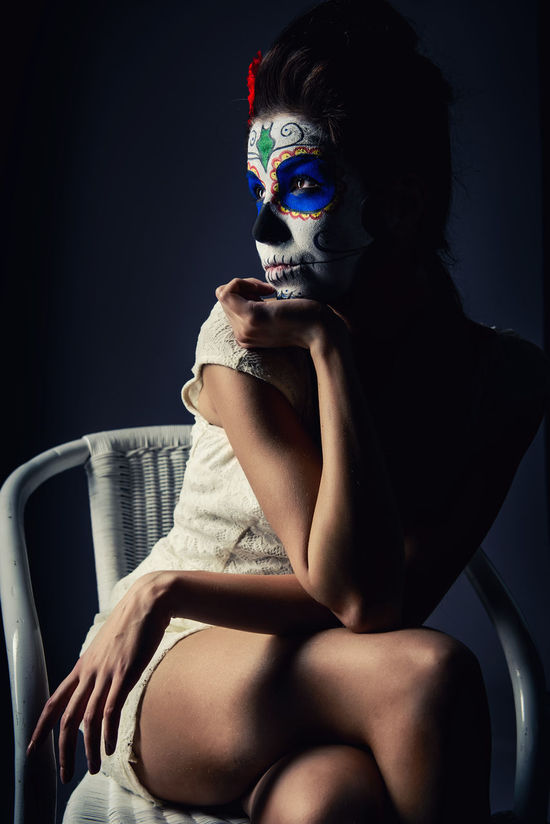 Day of the dead girl with sugar skull make-up Day Of The Dead Face Painted Halloween Horror Makeup Mexican Culture Mortality Sitting Woman Body Arts Day Of The Dead Skull Face Paint Female Girl Macabre Art Mexican Holidays One Person Skeleton Makeup Sugar Skull Voodoo Young Adult