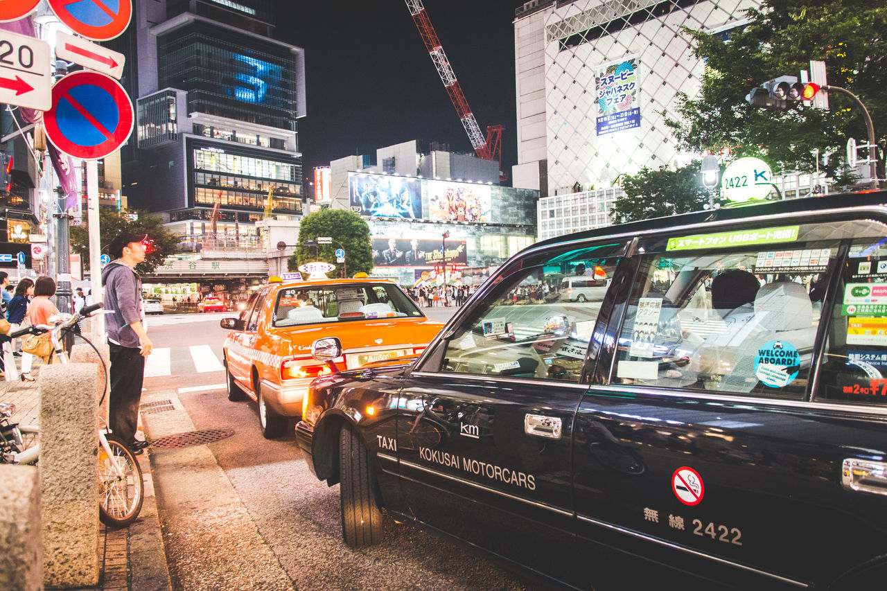 car, city, city life, building exterior, illuminated, architecture, street, transportation, city street, night, outdoors, land vehicle, yellow taxi, built structure, travel destinations, real people, modern, large group of people, crowd, people