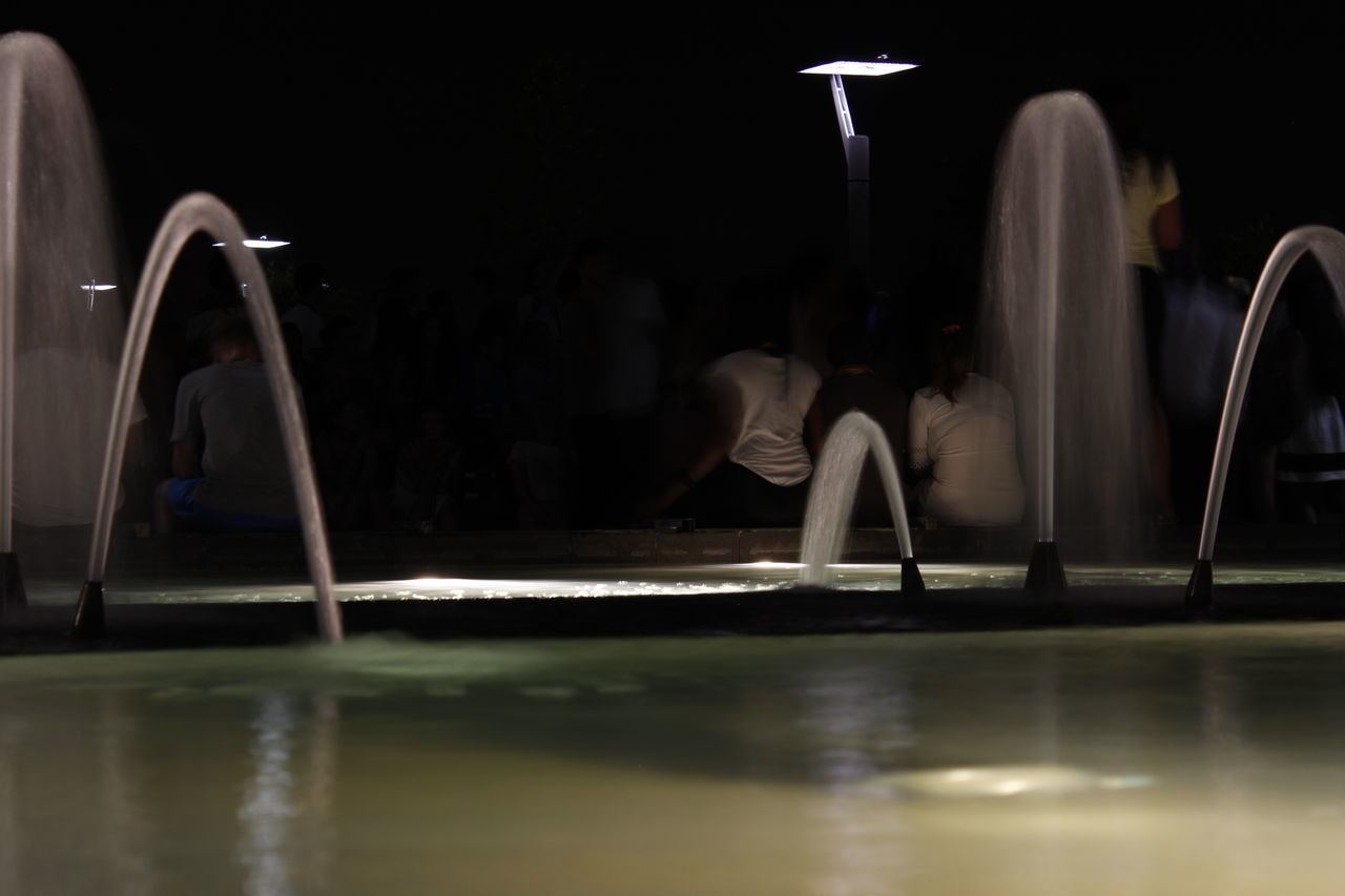 indoors, illuminated, water, arts culture and entertainment, real people, night, one person, people