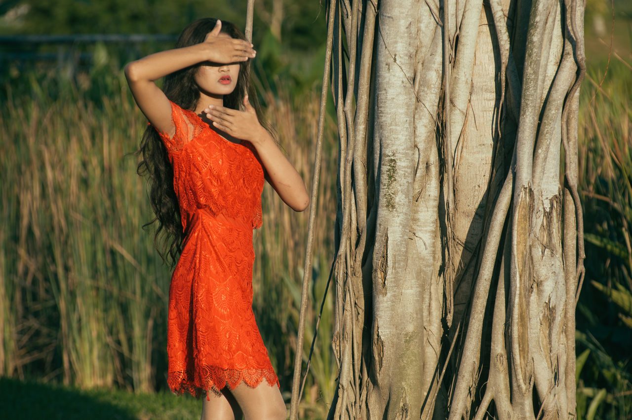 Adult Adults Only Beautiful People Beauty Dress Fashion Glamour Grass Human Body Part Long Hair Nature One Person One Woman Only One Young Woman Only Only Women Outdoors People Portrait Red Standing Summer Three Quarter Length Tree Young Adult Young Women