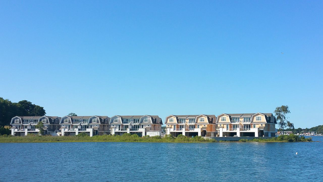 River In Front Of Houses Against Clear Sky