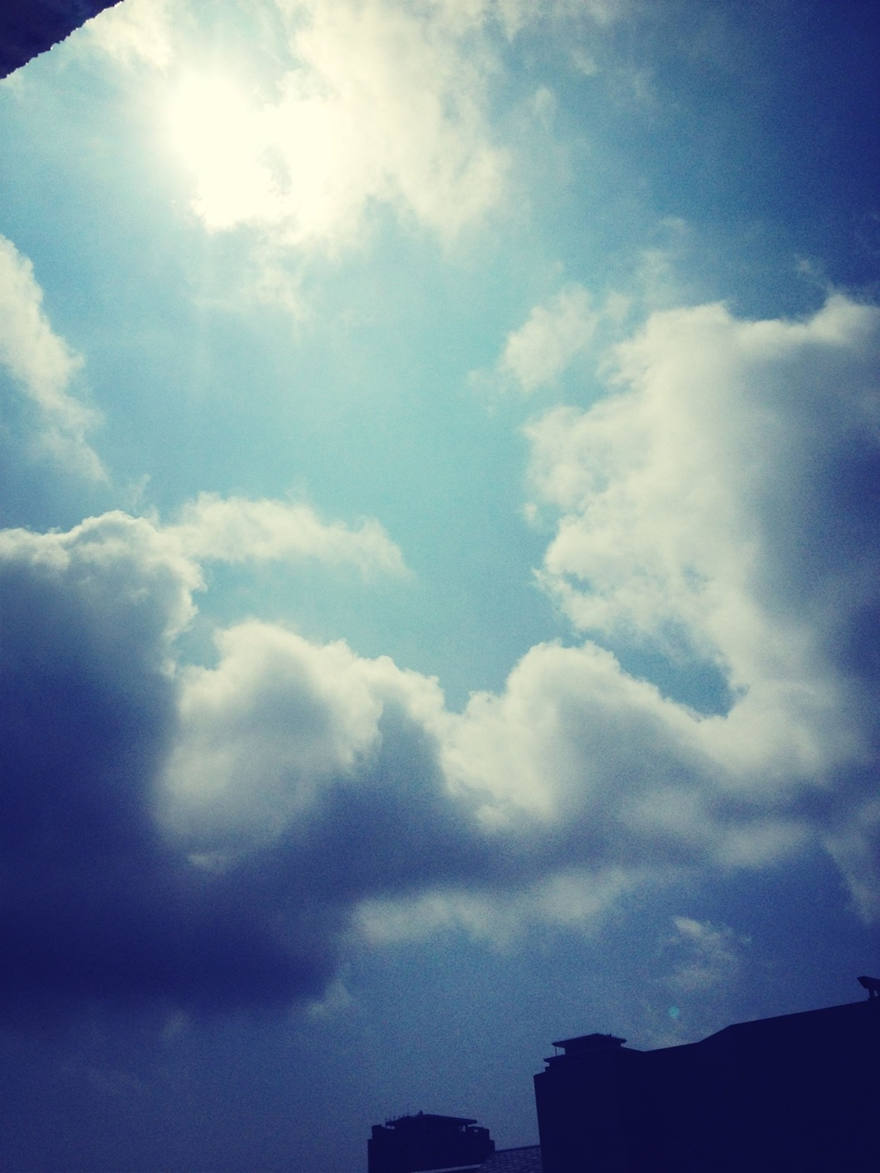 low angle view, sky, cloud - sky, building exterior, architecture, built structure, silhouette, cloudy, cloud, blue, high section, nature, beauty in nature, sunlight, outdoors, cloudscape, no people, building, day, weather