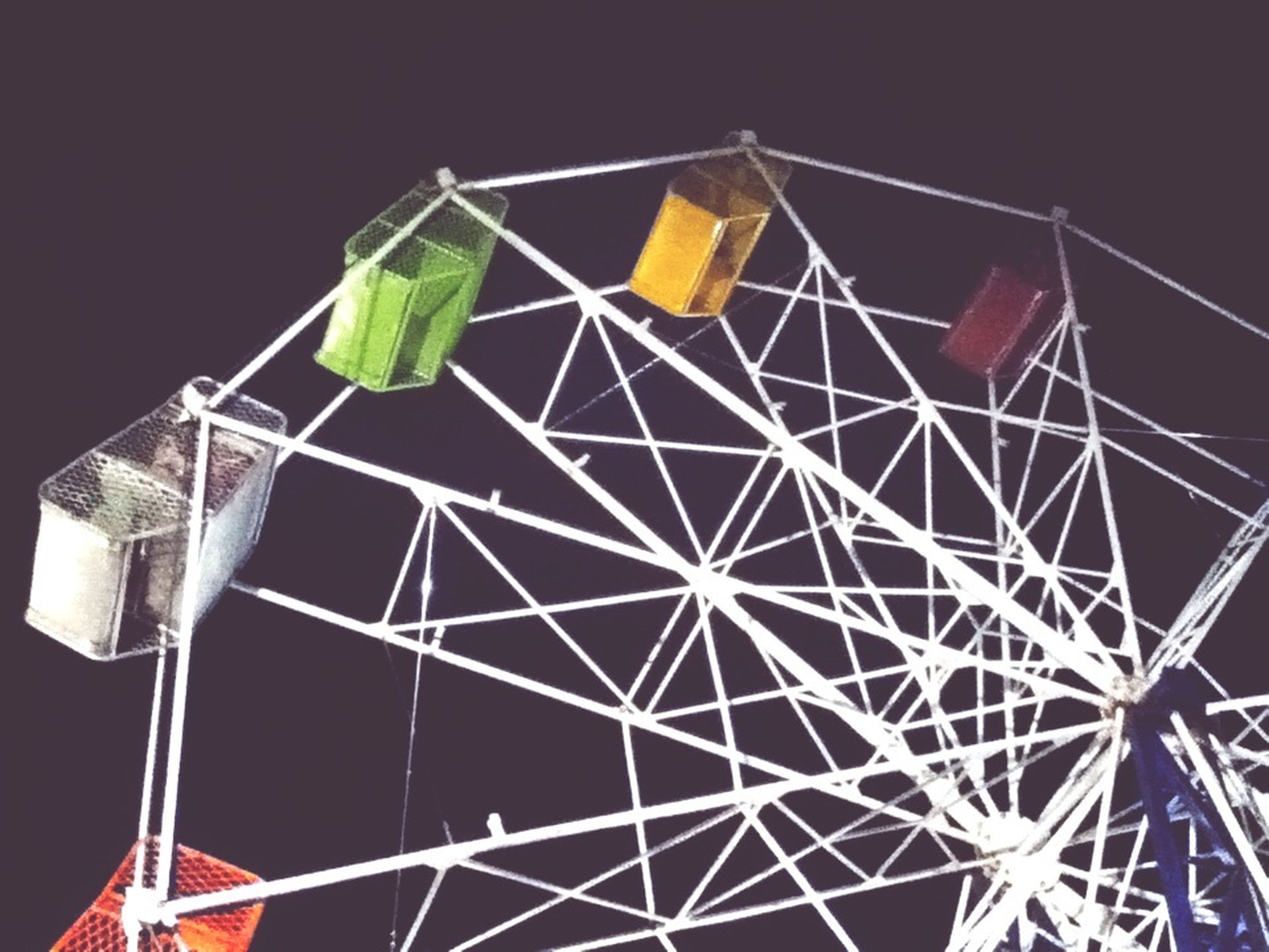 low angle view, metal, pattern, arts culture and entertainment, no people, night, amusement park, amusement park ride, multi colored, outdoors, yellow, sky, close-up, ferris wheel, clear sky, built structure, metallic, green color, illuminated