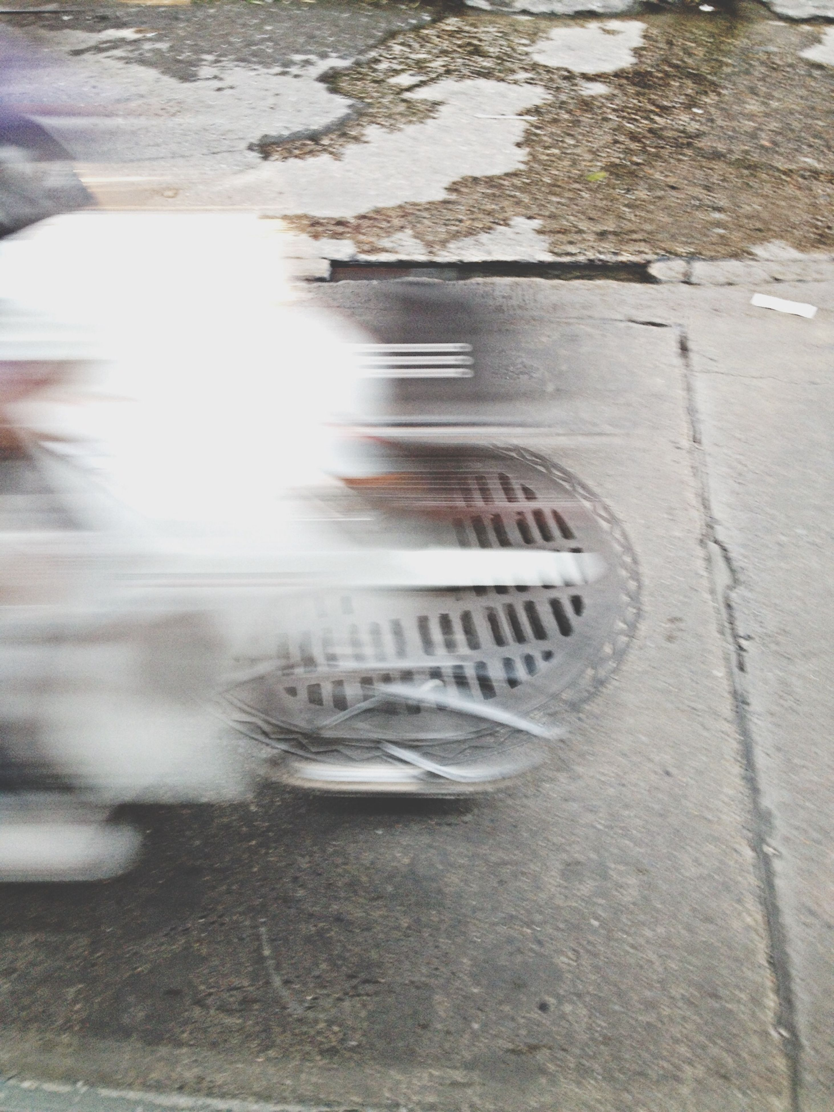 street, close-up, reflection, motion, road, water, day, wet, no people, transportation, outdoors, high angle view, sunlight, blurred motion, sidewalk, glass - material, focus on foreground, asphalt, transparent