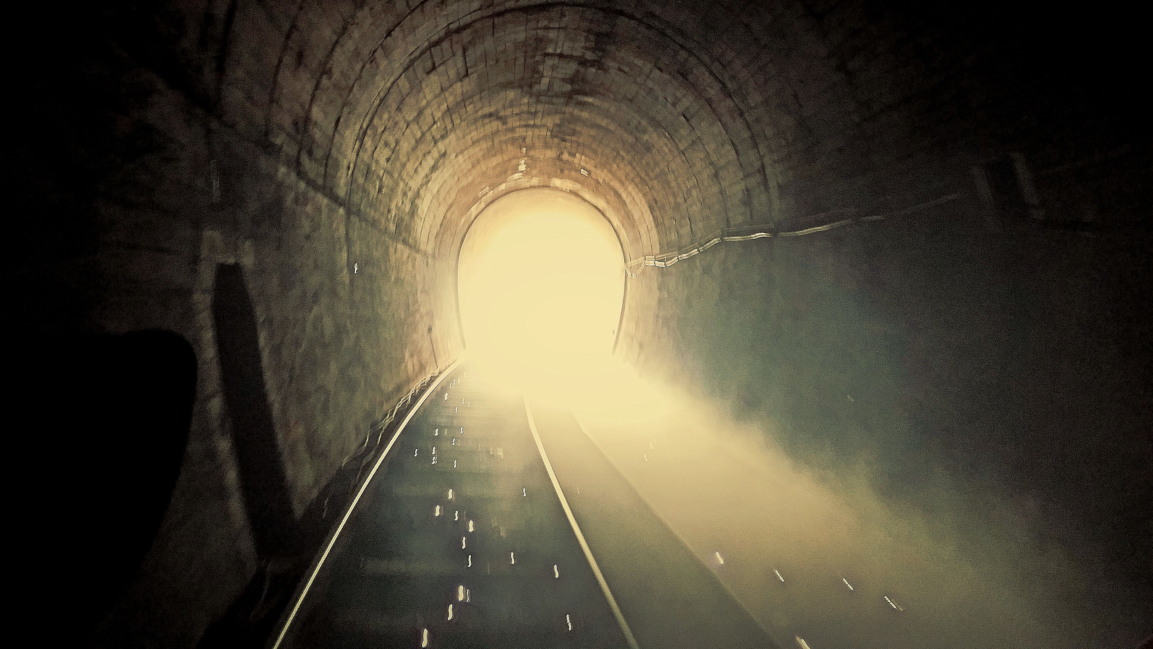 indoors, tunnel, the way forward, arch, diminishing perspective, vanishing point, illuminated, built structure, architecture, transportation, dark, light at the end of the tunnel, wall - building feature, lighting equipment, ceiling, light - natural phenomenon, no people, sunlight, silhouette, wall