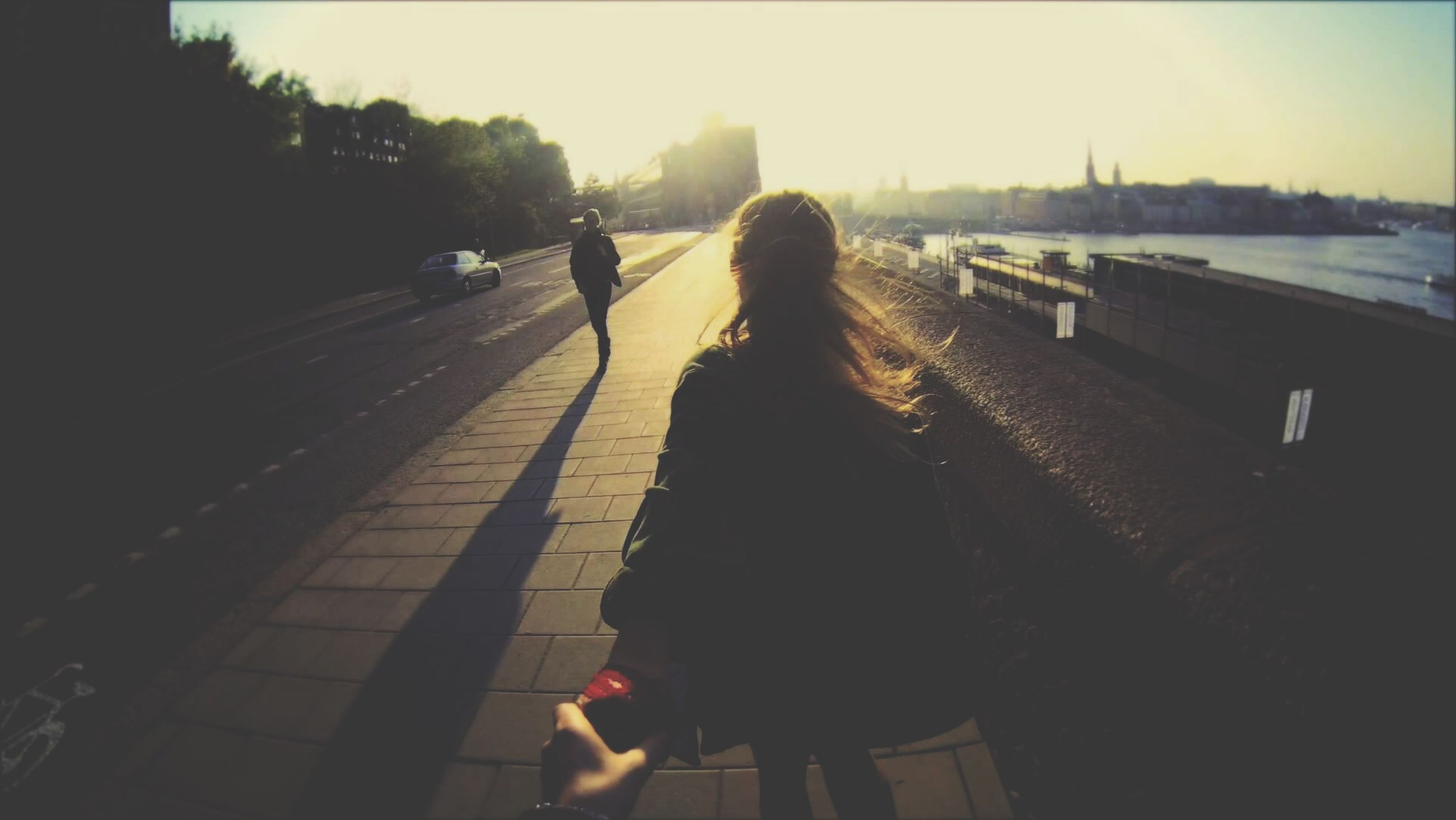 lifestyles, rear view, leisure activity, walking, full length, person, clear sky, silhouette, sunlight, togetherness, men, shadow, the way forward, street, standing, bonding, city life