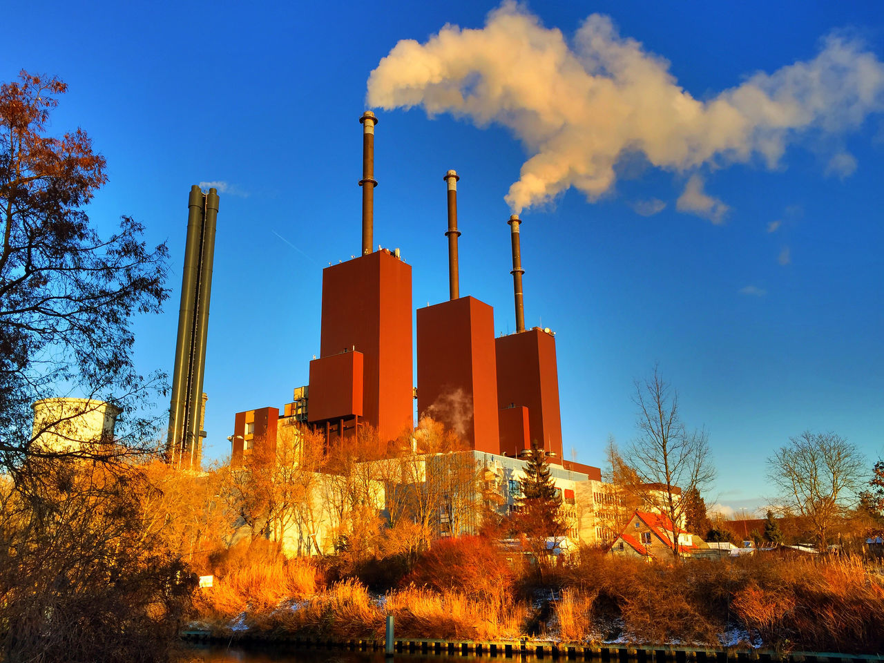 built structure, architecture, building exterior, smoke stack, tree, industry, sky, low angle view, factory, no people, outdoors, bare tree, blue, day, chimney, clear sky