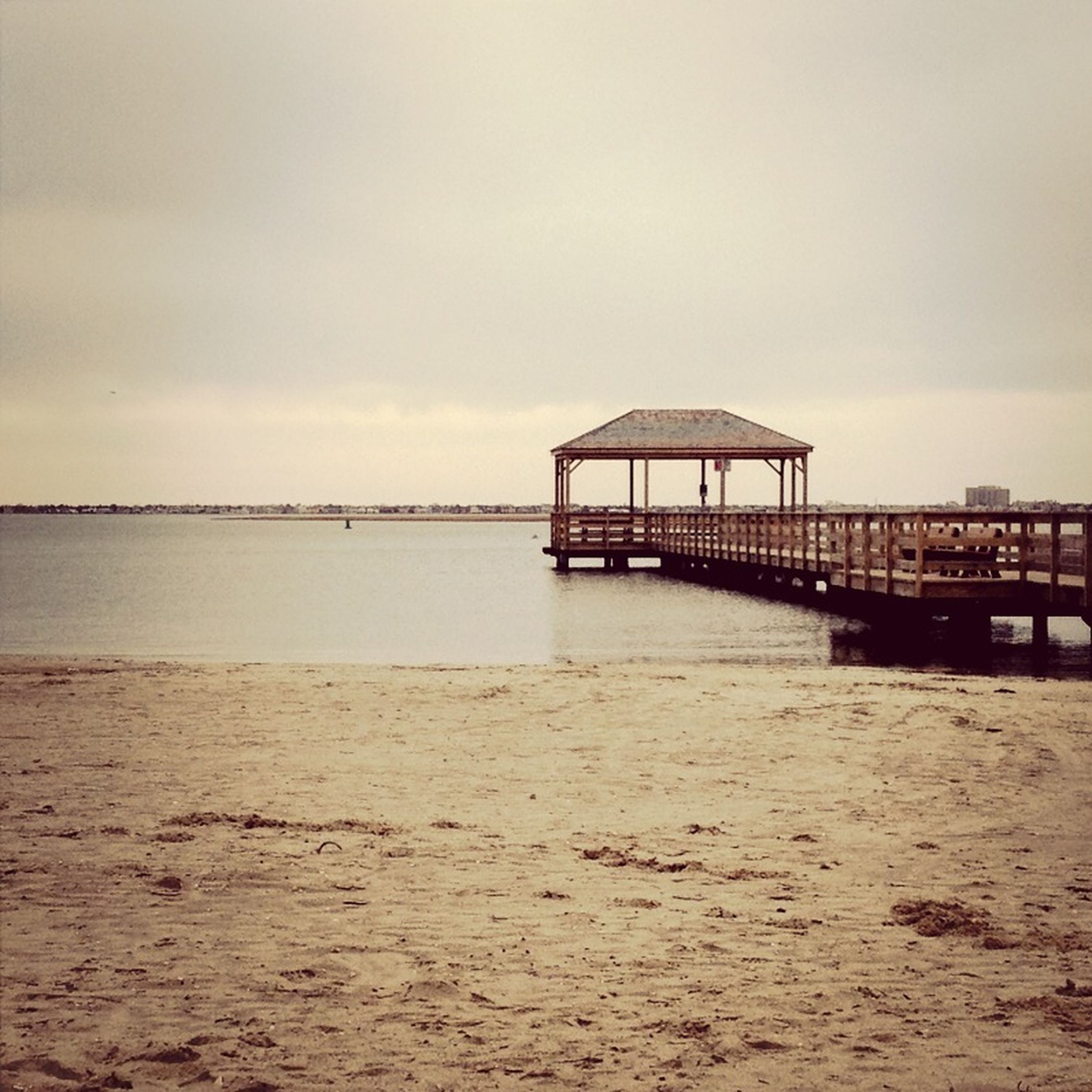 sea, water, beach, built structure, pier, sky, tranquil scene, tranquility, sand, architecture, scenics, shore, horizon over water, nature, beauty in nature, wood - material, idyllic, jetty, calm, outdoors