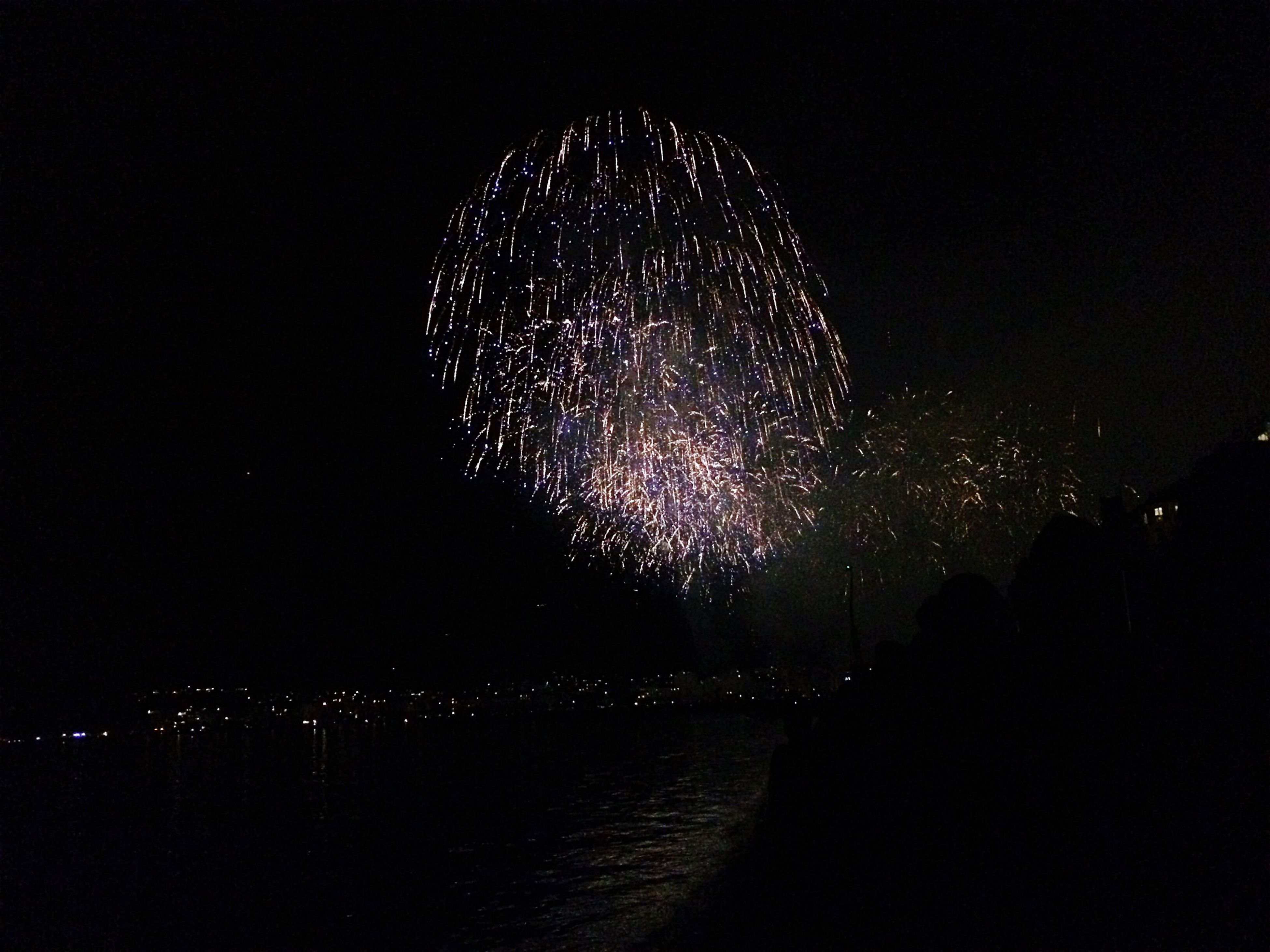 night, illuminated, firework display, arts culture and entertainment, celebration, long exposure, glowing, motion, exploding, firework - man made object, event, sparks, low angle view, sky, firework, city, blurred motion, dark, clear sky, lighting equipment