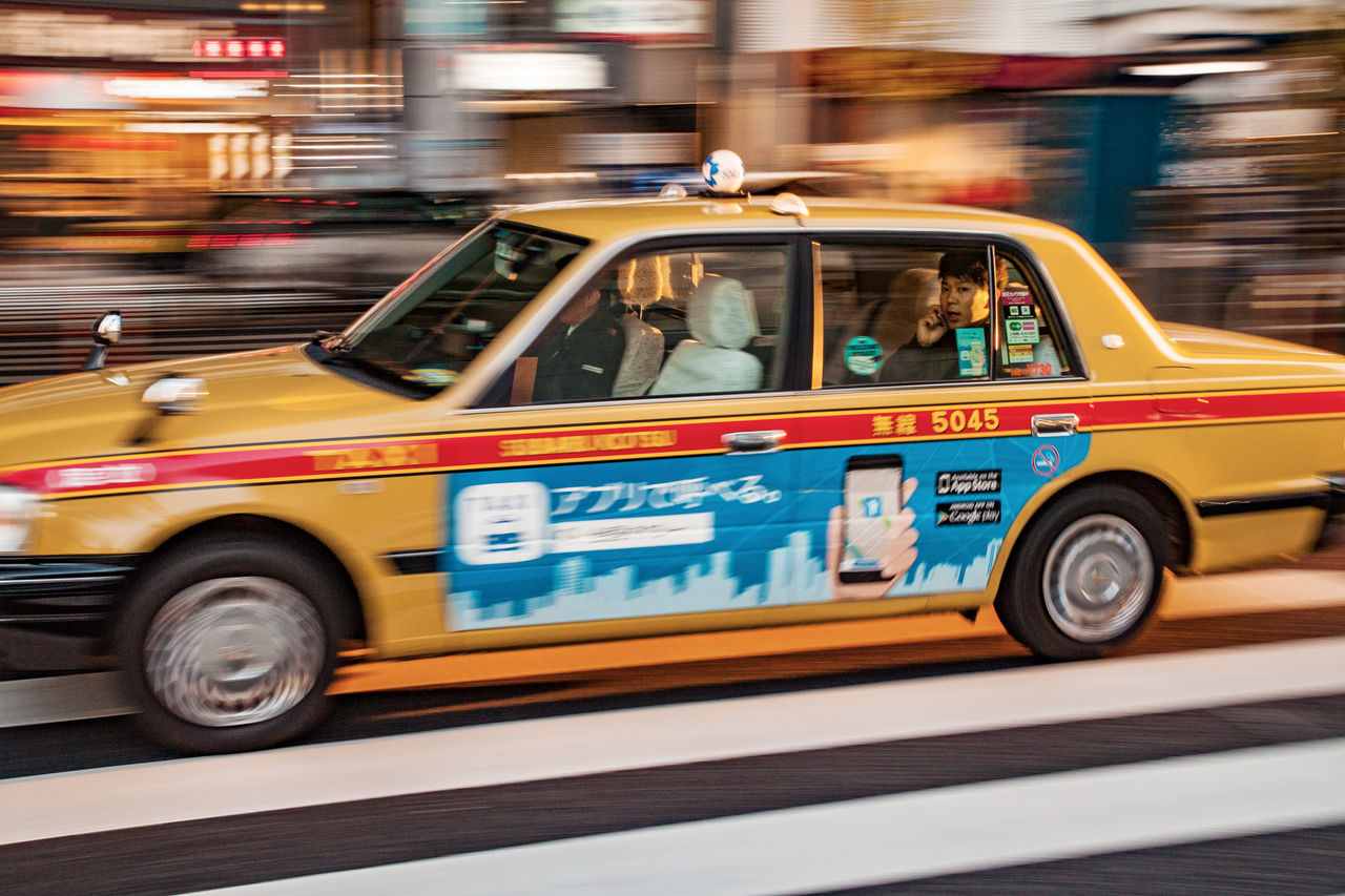 A taxy speeds at Roppongi, Tokyo Bus City Close-up Day Japan Japanese  Mobile Outdoors Passenger Phone Roppongi Taxi Tokyo Transportation Urban Yellow Taxi Welcome Weekly