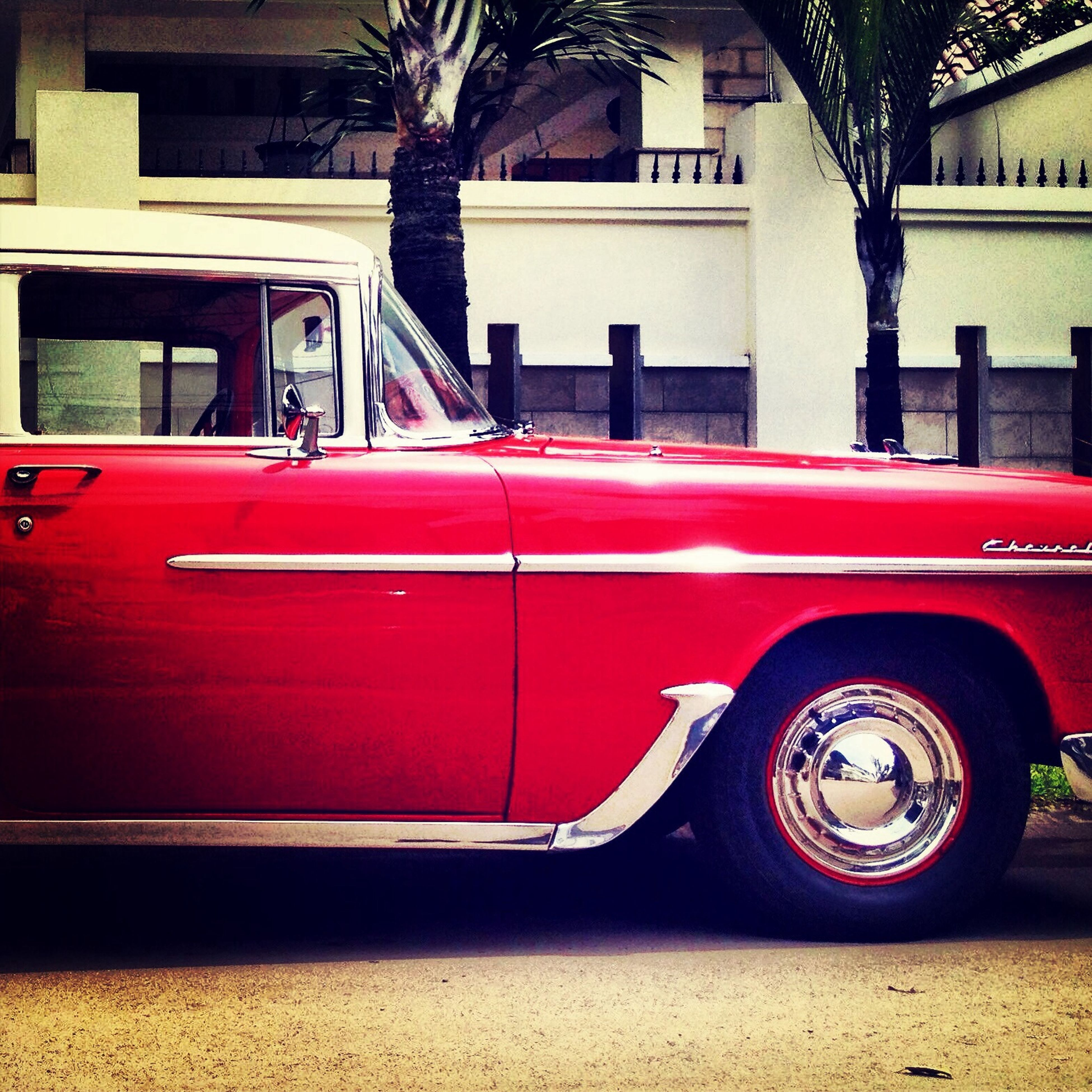 land vehicle, car, mode of transport, transportation, building exterior, architecture, built structure, street, red, tree, city, stationary, parking, side view, outdoors, sitting, vintage car, parked, day, window