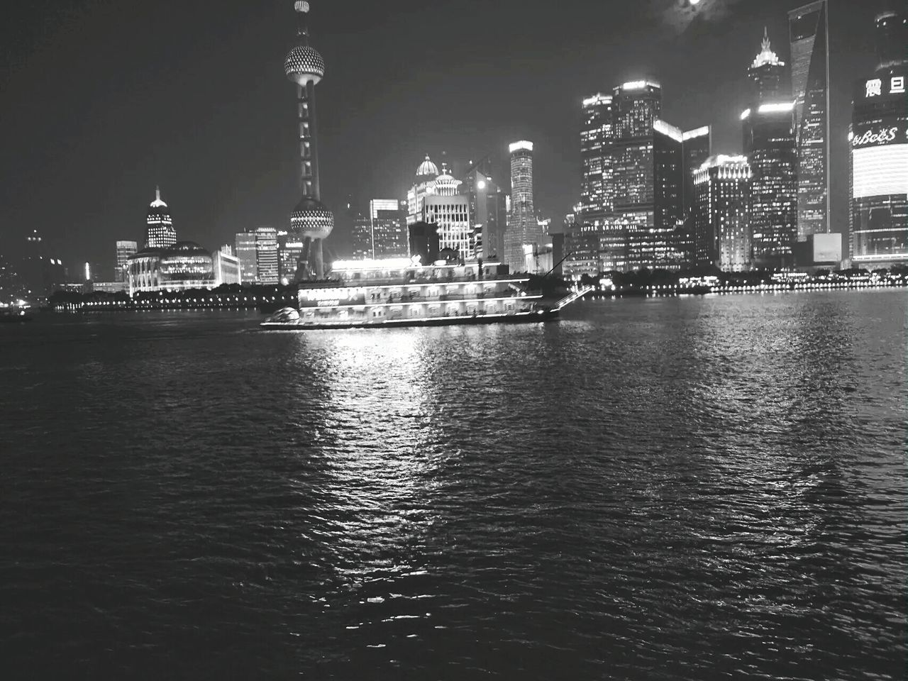 building exterior, architecture, night, built structure, illuminated, water, waterfront, city, travel destinations, outdoors, tourism, skyscraper, nautical vessel, sky, urban skyline, no people, cityscape, nature
